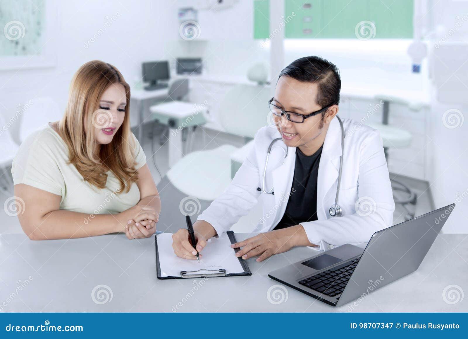 Doutor masculino que escreve uma prescrição a seu paciente