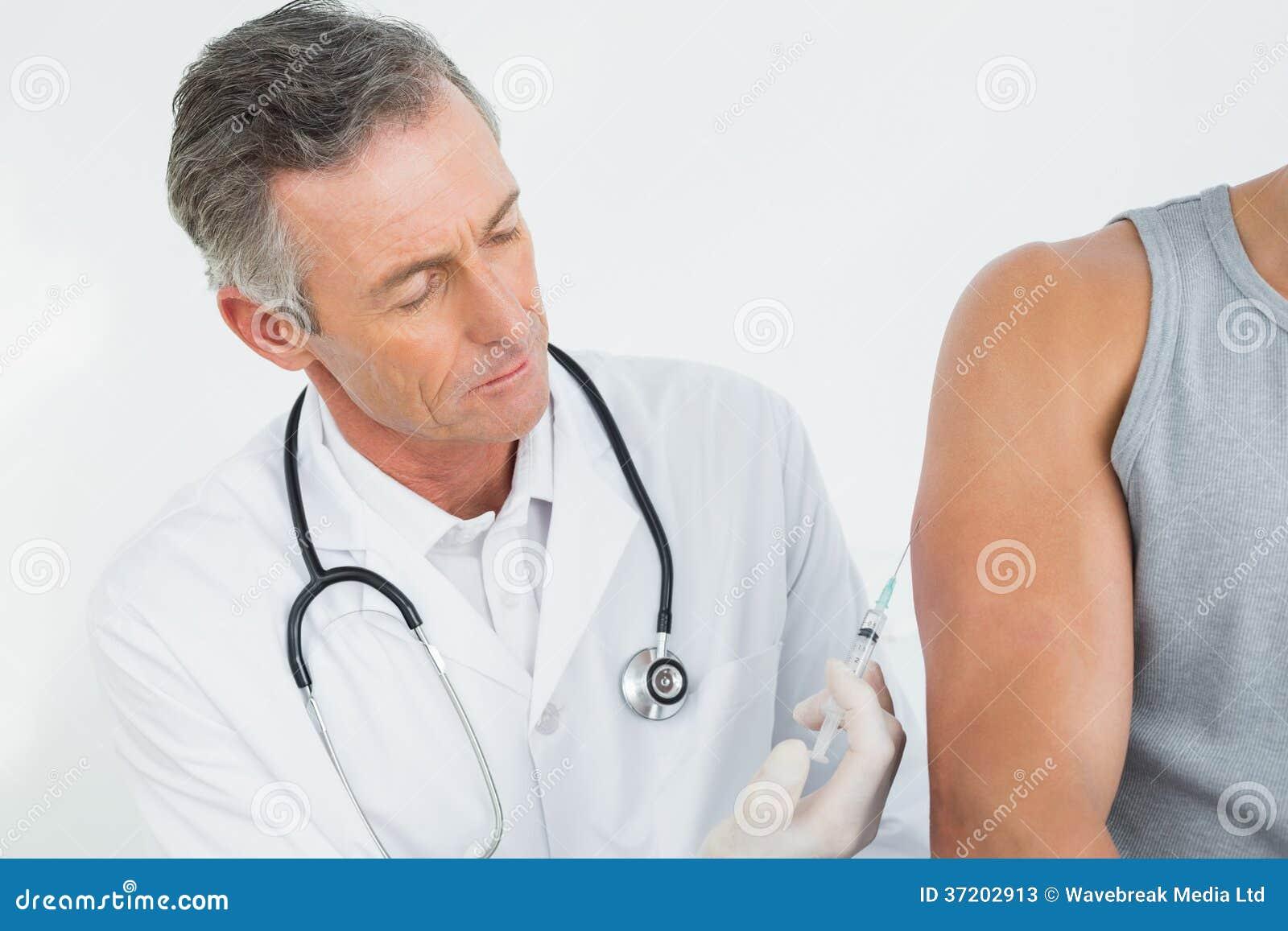 Doutor masculino que injeta um braço dos pacientes