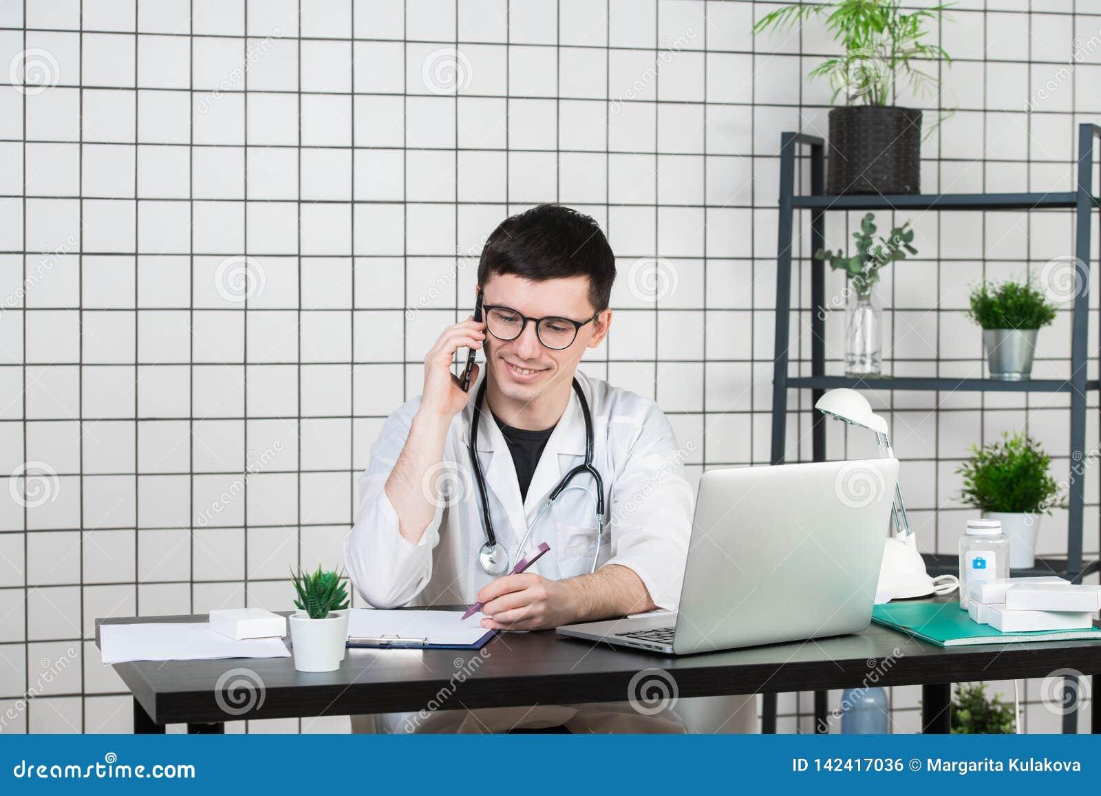 Doutor masculino que usa o telefone ao trabalhar no computador na tabela na clínica