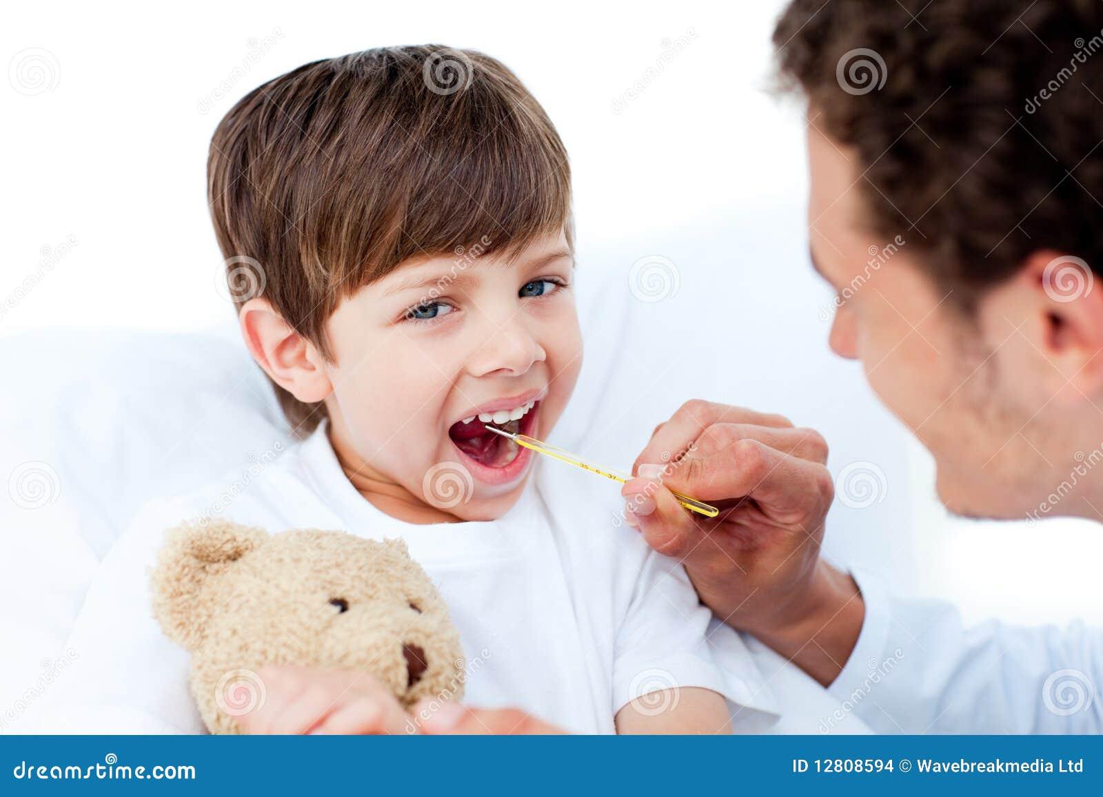 Doutor novo que toma a temperatura do rapaz pequeno