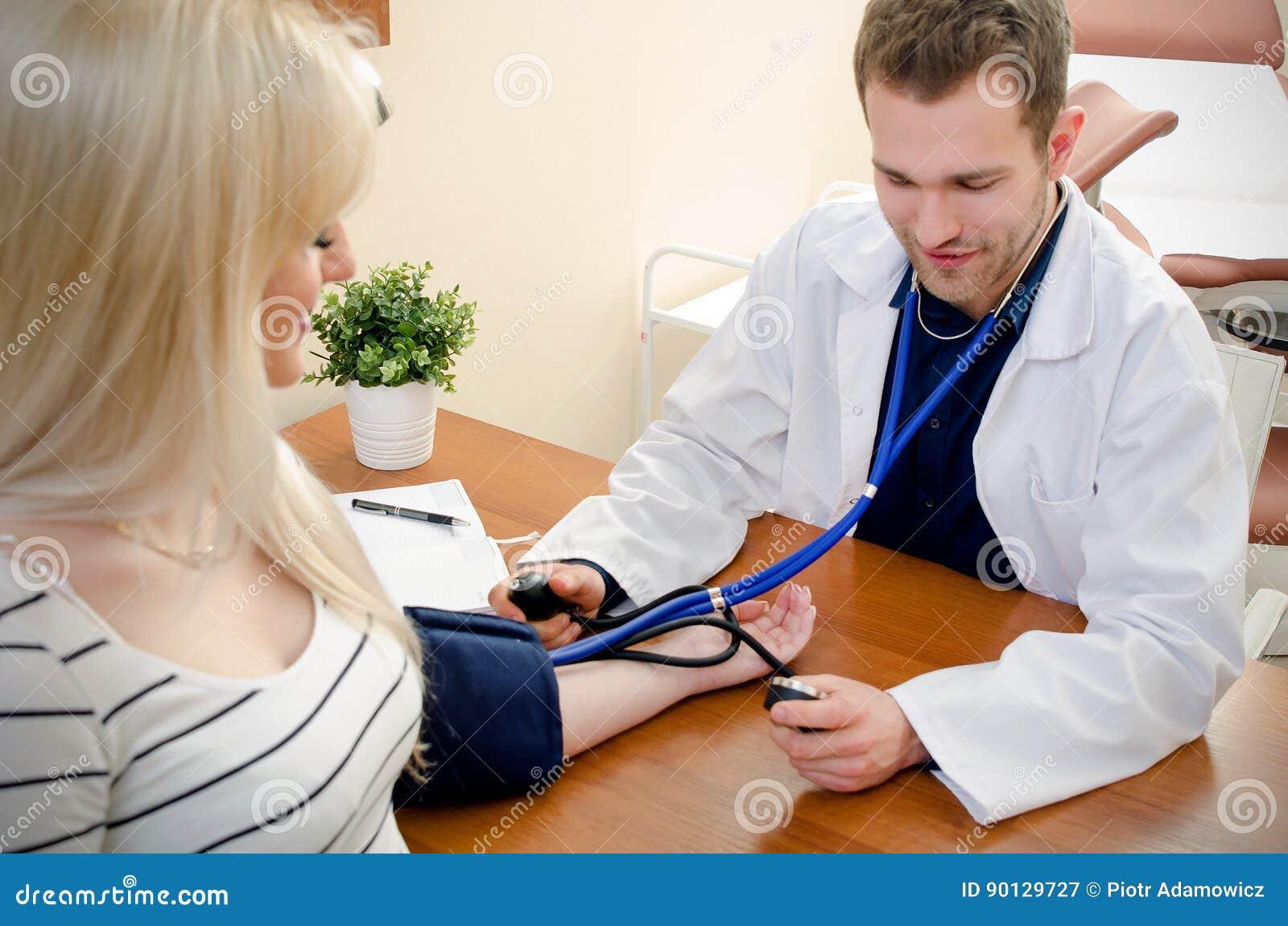 Doutor novo que verifica a pressão sanguínea do paciente fêmea