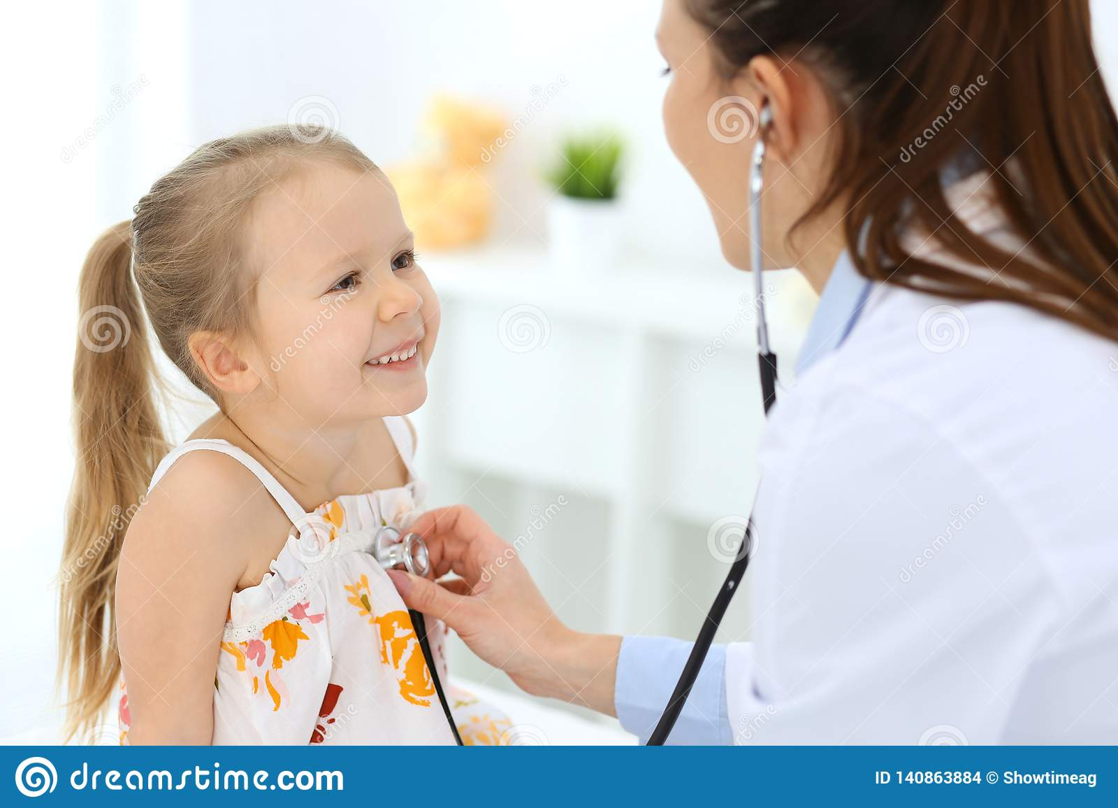 Doutor que examina uma menina pelo estetoscópio Paciente de sorriso feliz da criança na inspeção médica usual Medicina e