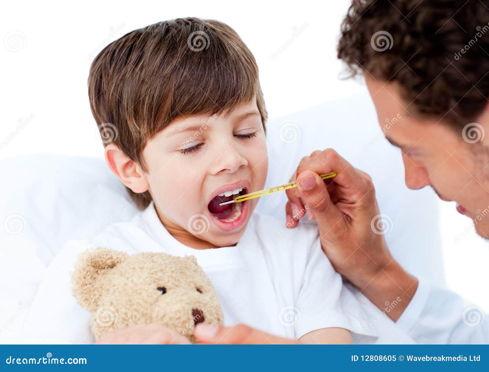 Doutor que toma a temperatura do rapaz pequeno