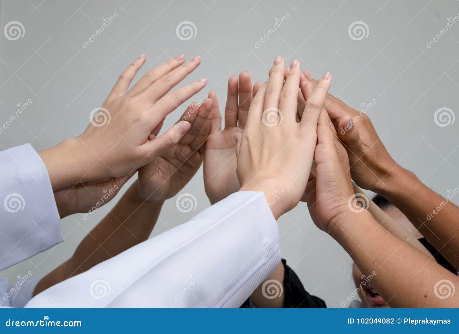 Doutores e enfermeiras em uma equipa médica que empilha as mãos