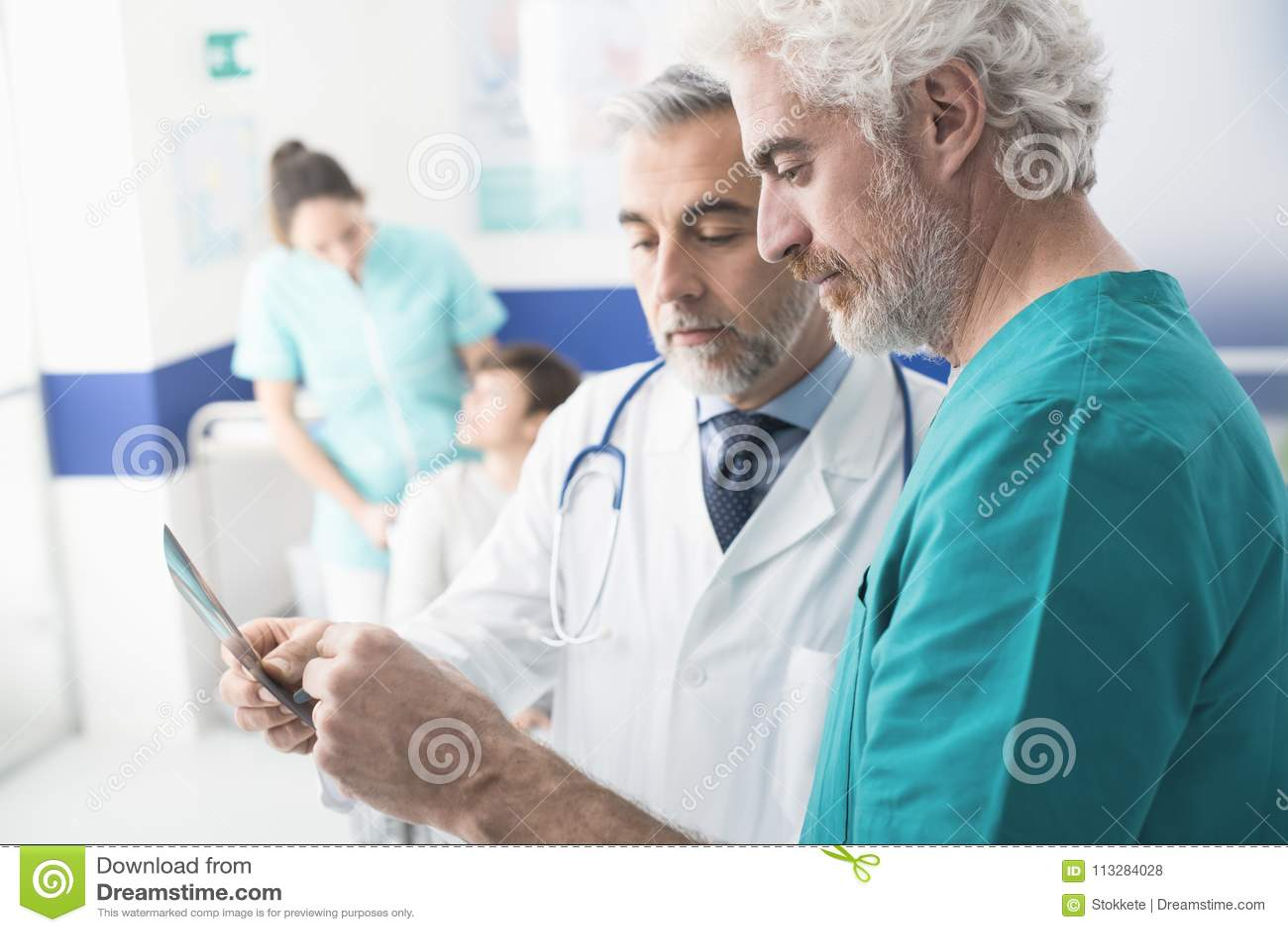 Doutores profissionais que examinam o raio X paciente do ` s