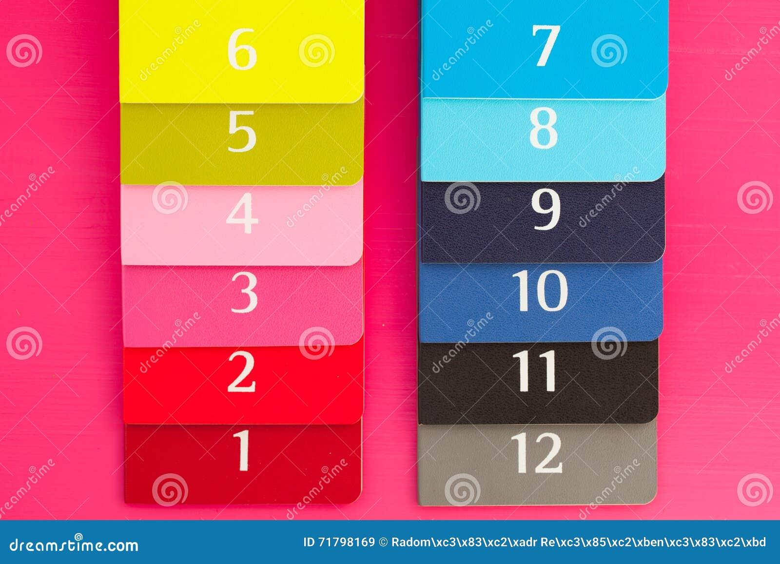 Douze journaux intimes différents de couleur sur un bureau en bois
