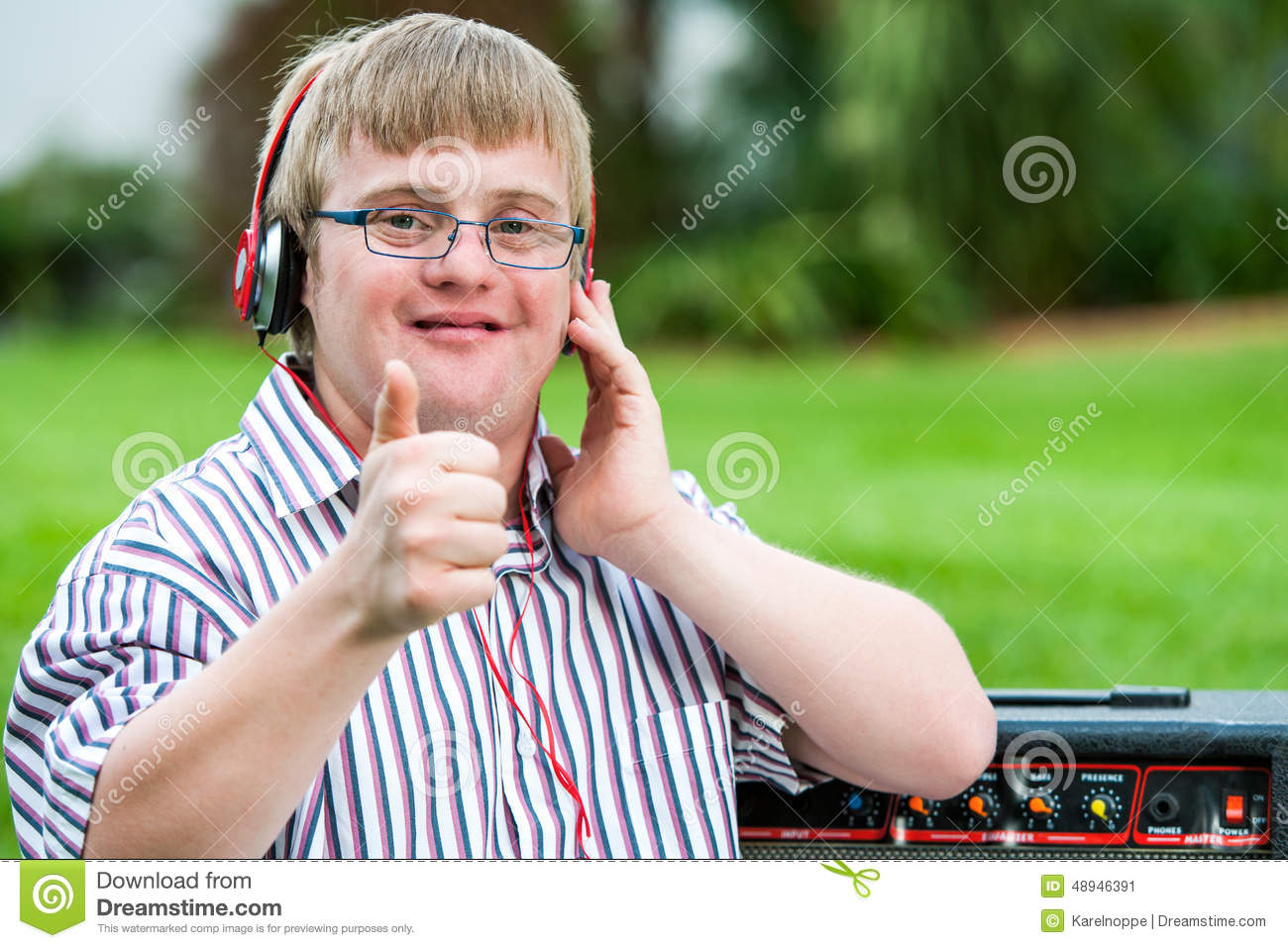 Down Syndrome Boy With Headset Doing Thumbs Up  Stock Image