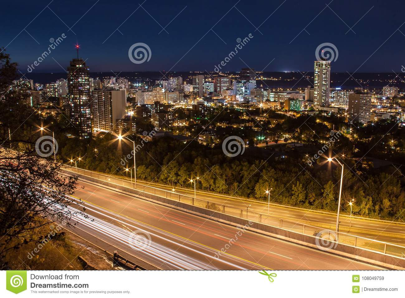 Downtown skyline and light trails from cars at night in Hamilton, Ontario