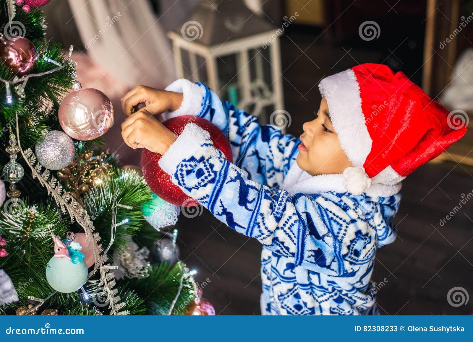 Dräkt Santa Claus som för afrikansk amerikanpojkepåklädd dekorerar en julgran