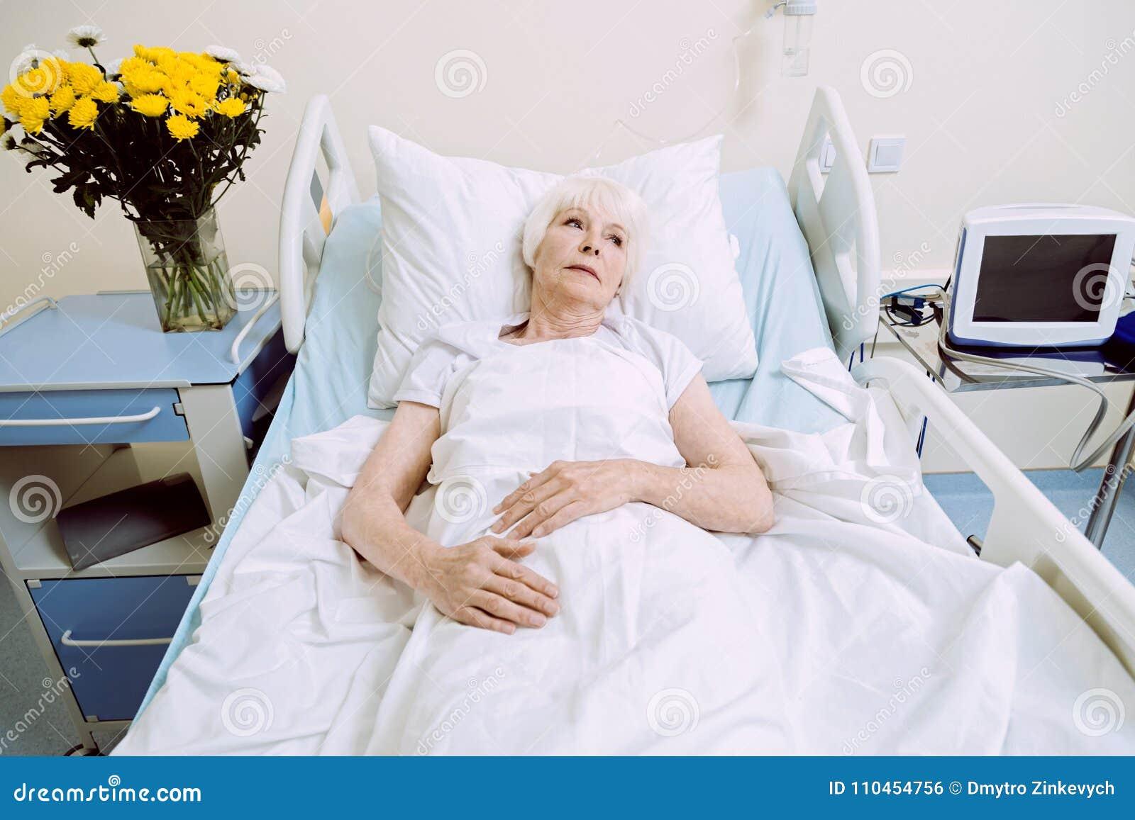 Drömlik äldre kvinna i sjukhussäng som tänker om något