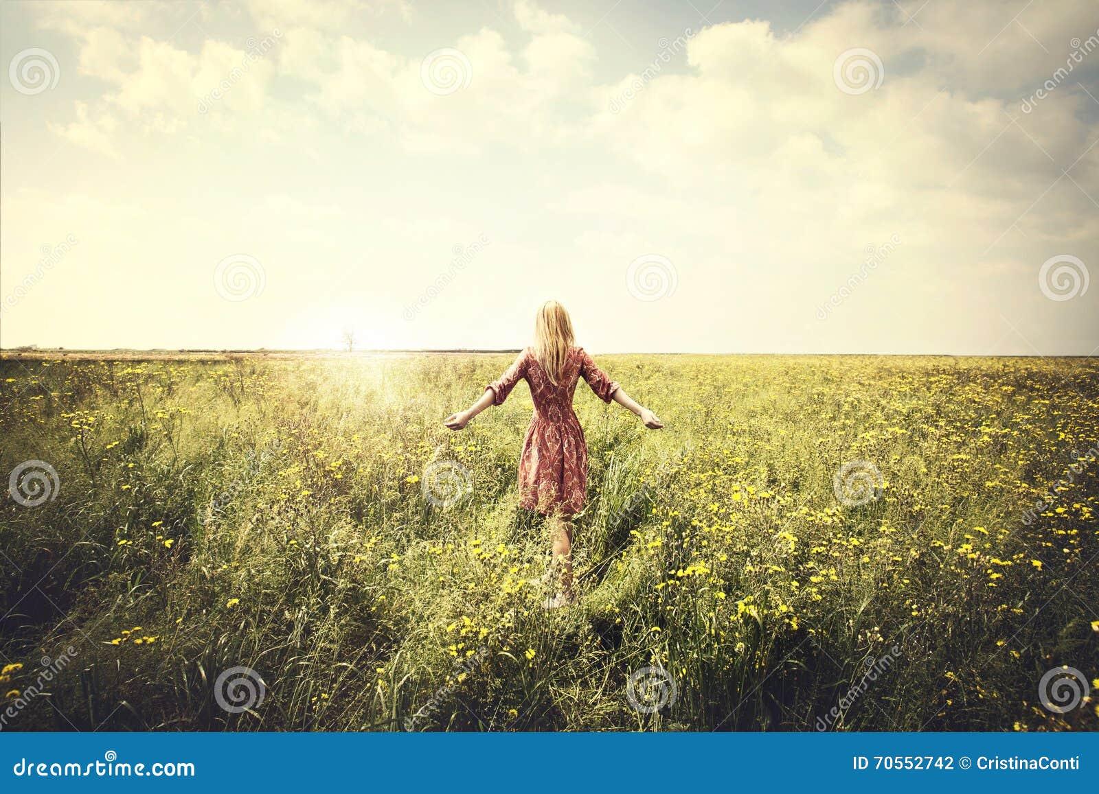 Drömlik kvinna som går i natur in mot solen