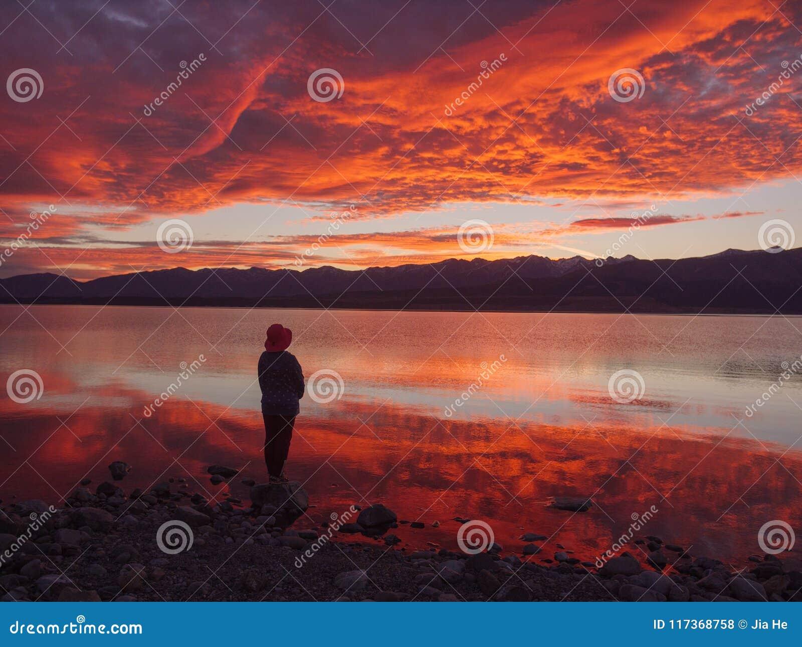 Drömmare kontur av kvinnaanseendet längs sjön på solnedgången, mänsklig styrka, psykologibegrepp
