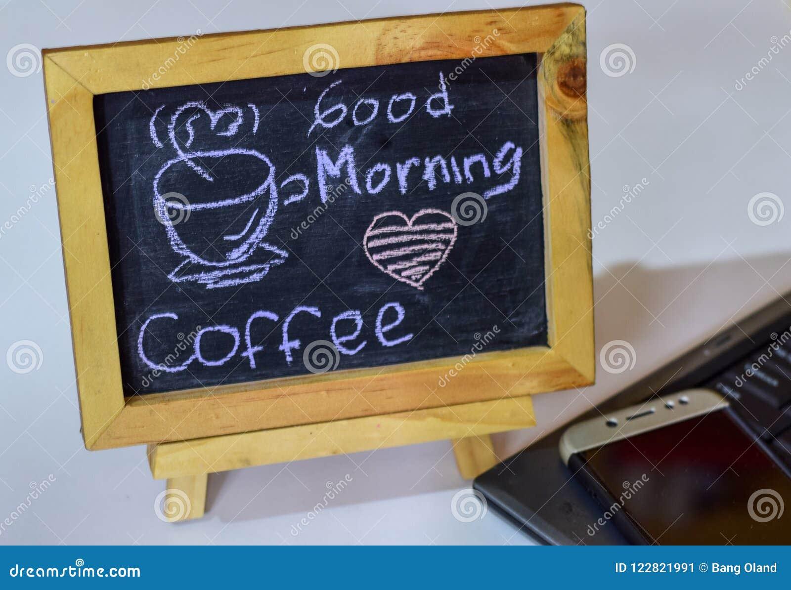 Drücken Sie den Kaffee des guten Morgens aus, der auf eine Tafel auf ihr und Smartphone, Laptop geschrieben wird
