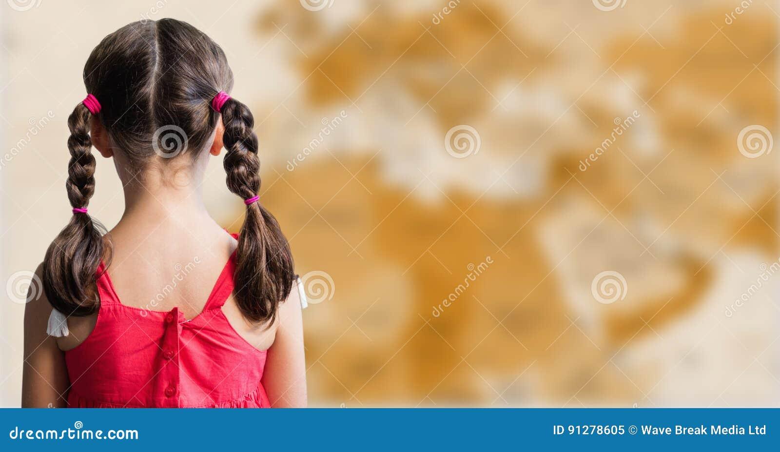 Dra tillbaka av flicka med flätade trådar mot oskarp brun översikt
