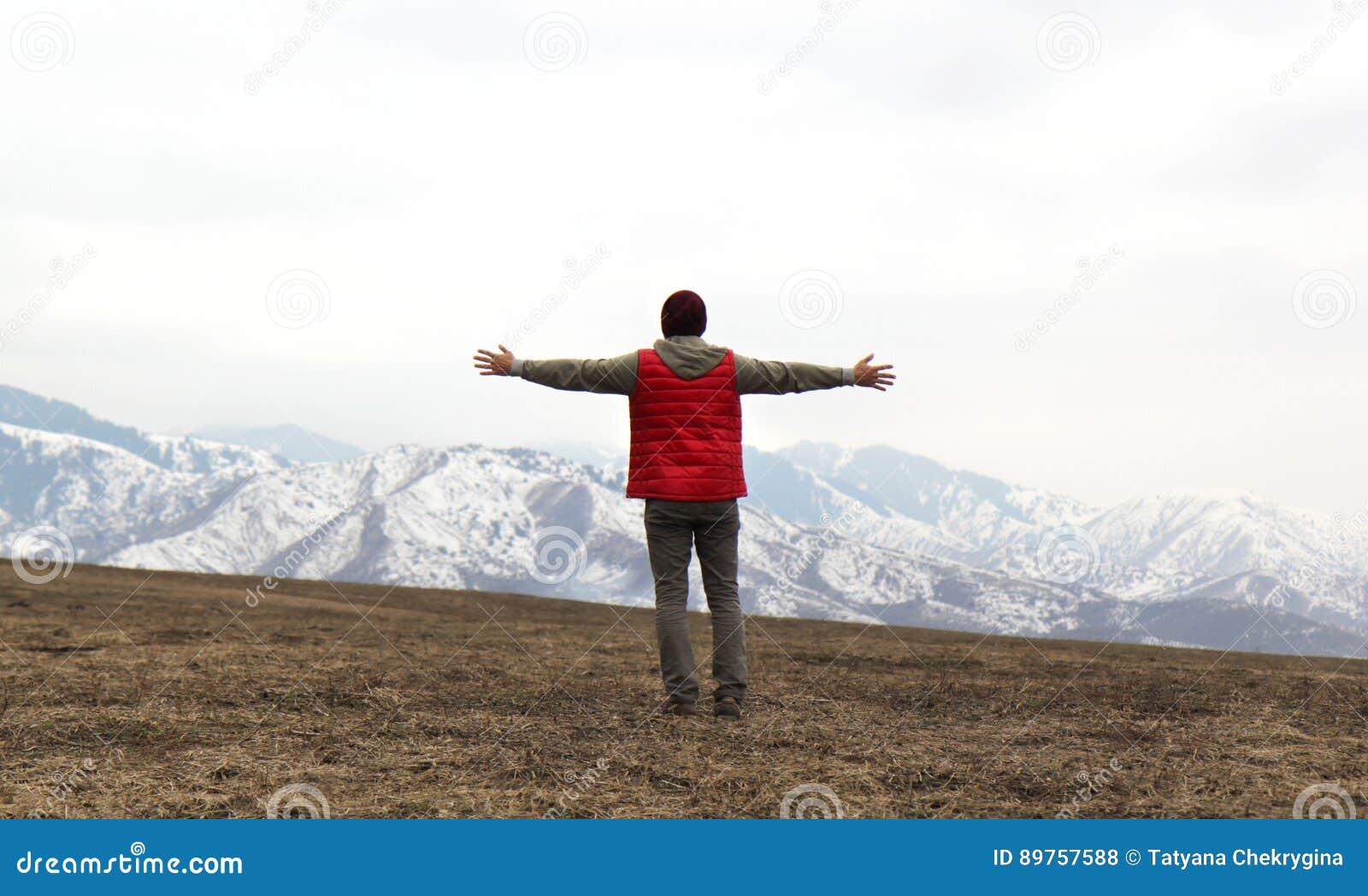 Dra tillbaka av man i röd waistcoat med händer till sidan på bergbakgrunden