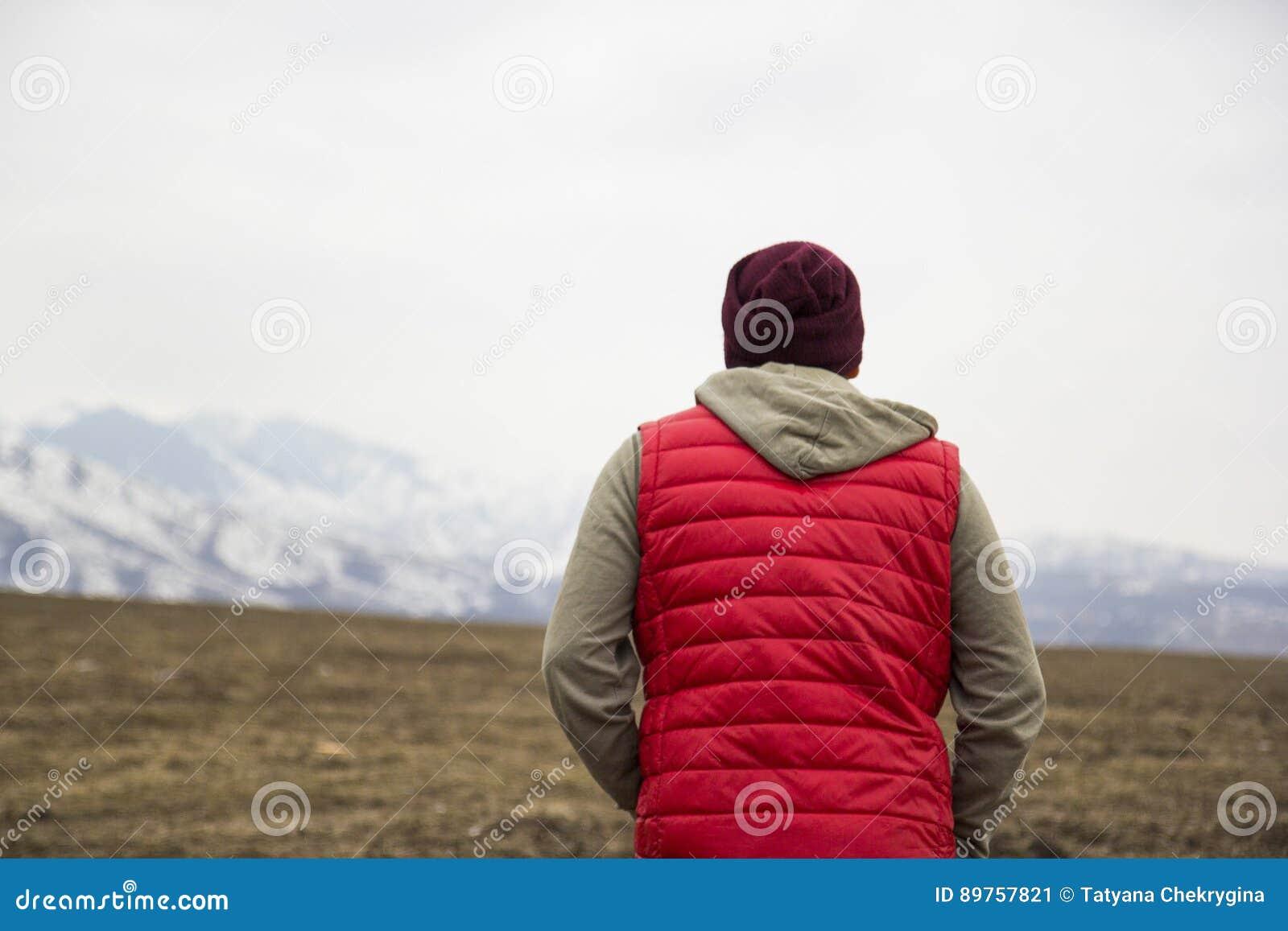 Dra tillbaka av man i röd waistcoat på bergbakgrunden