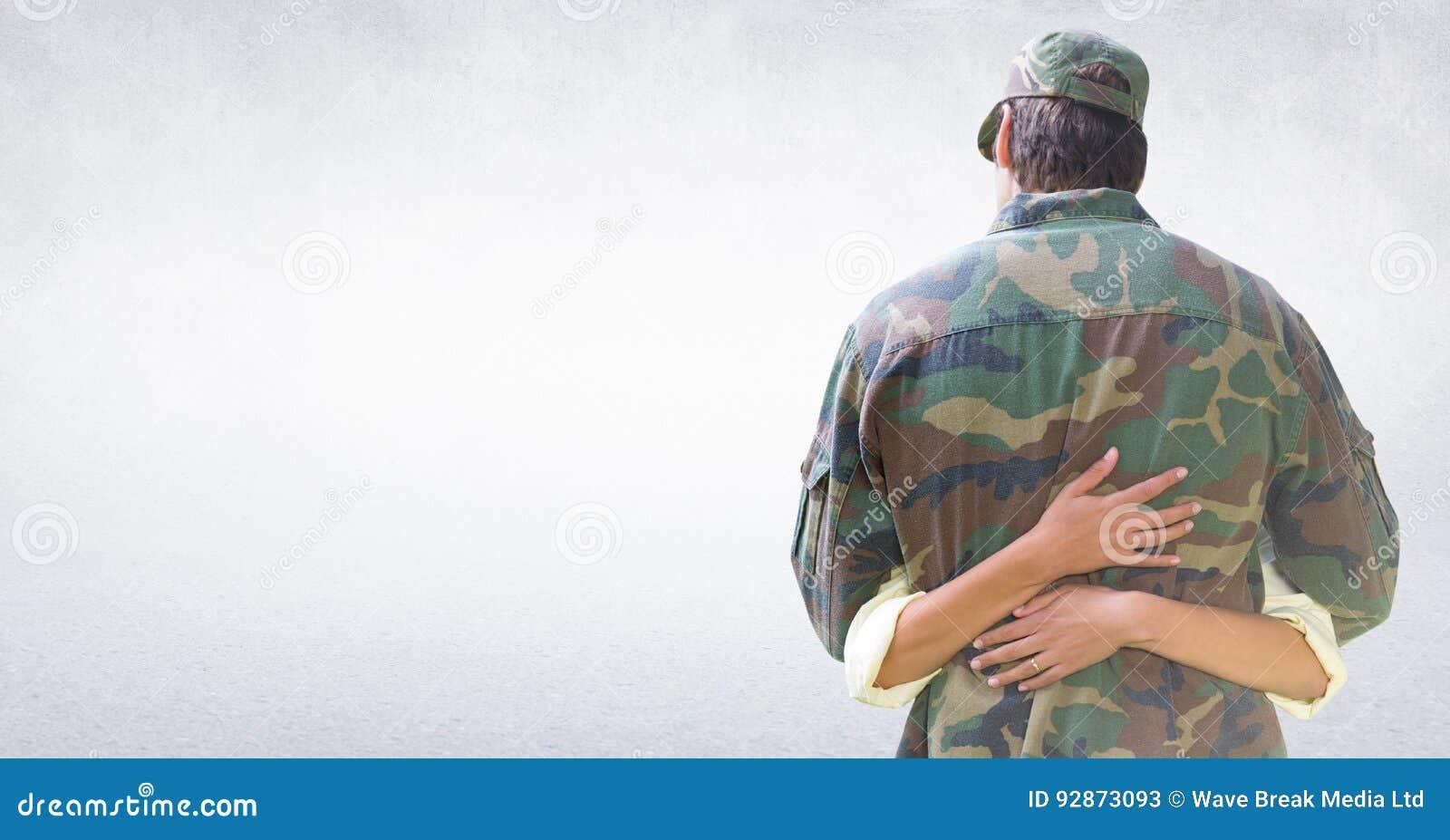 Dra tillbaka av soldaten som kramar mot den vita väggen