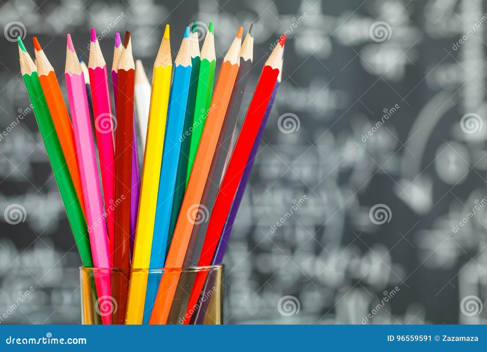 Dra tillbaka till skolabakgrund med färgrika filtpennor och suddiga matematikformler som är skriftliga vid vit krita på den svart