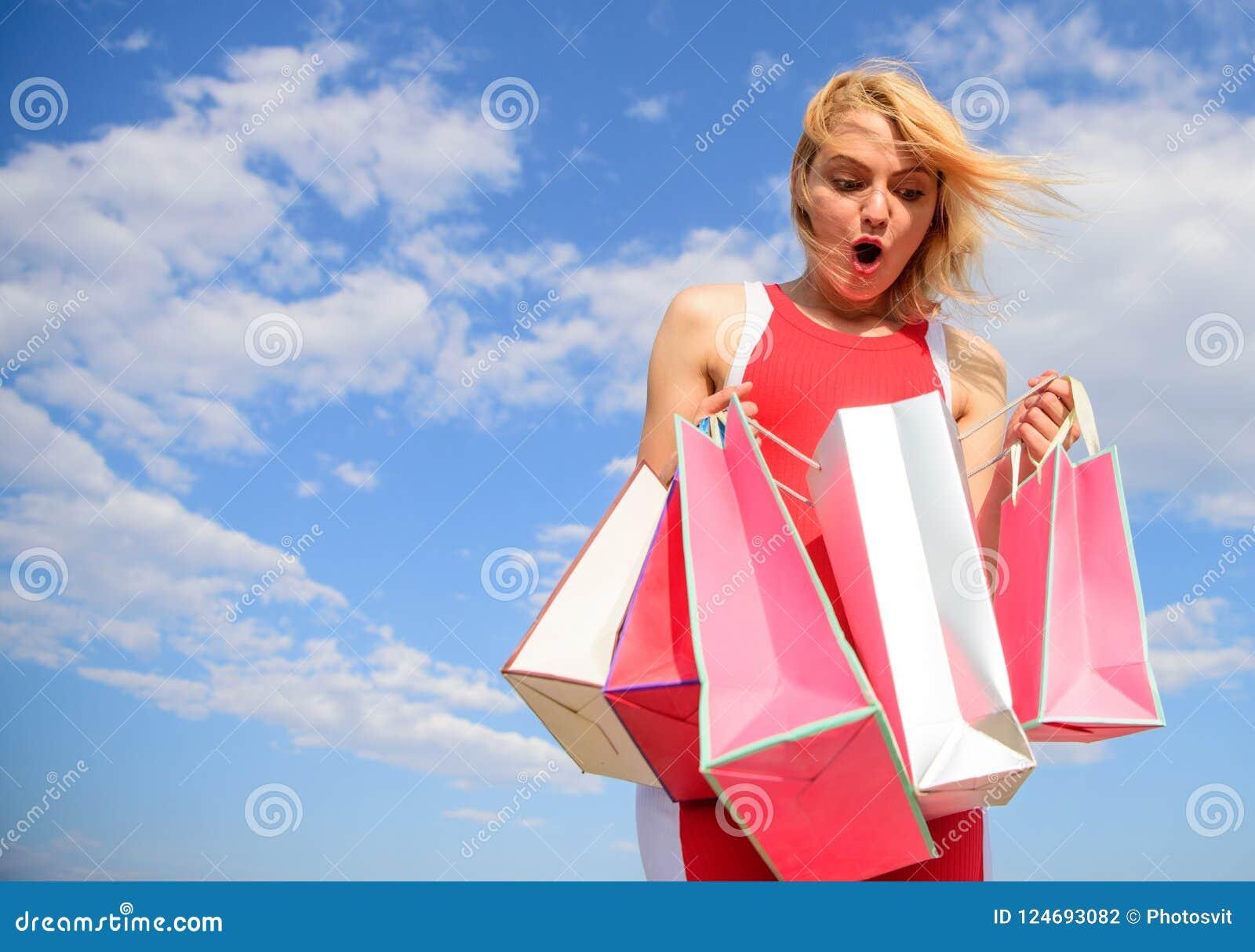 Draagt de vrouwen rode kleding bos het winkelen achtergrond van de zakken de blauwe hemel Meisje tevreden met aankopen Het winkel
