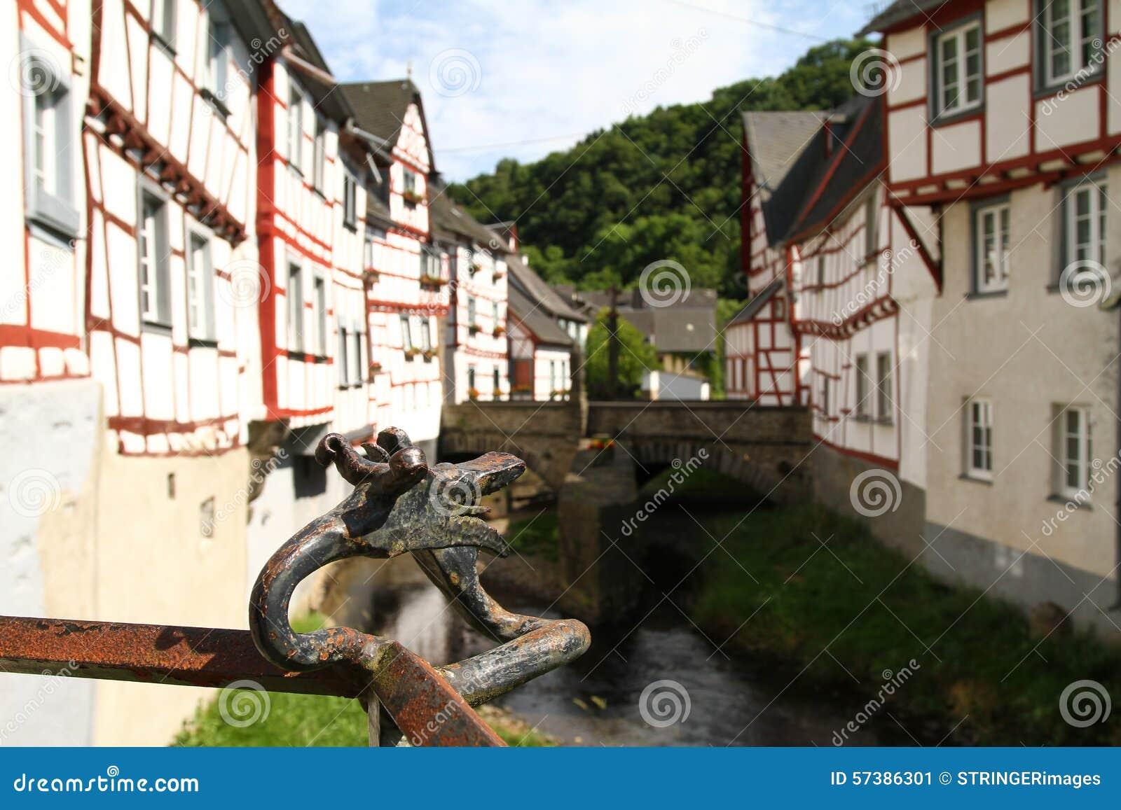 Draak hoofdtraliewerk voor een middeleeuwse dorpsachtergrond