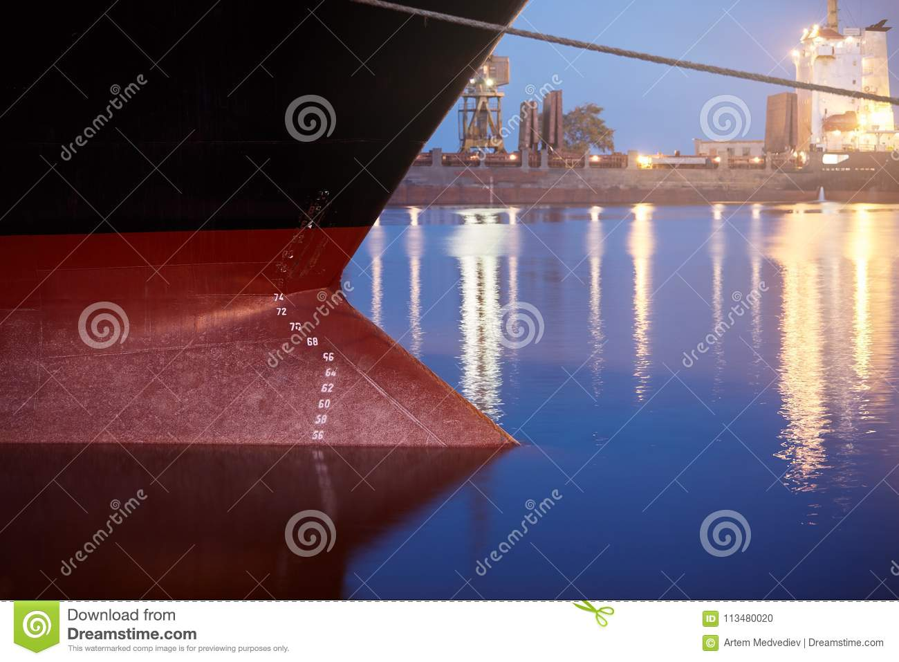 Draft marks on a ship - waterline numbers on bow and stern of a vessel at seaport at night