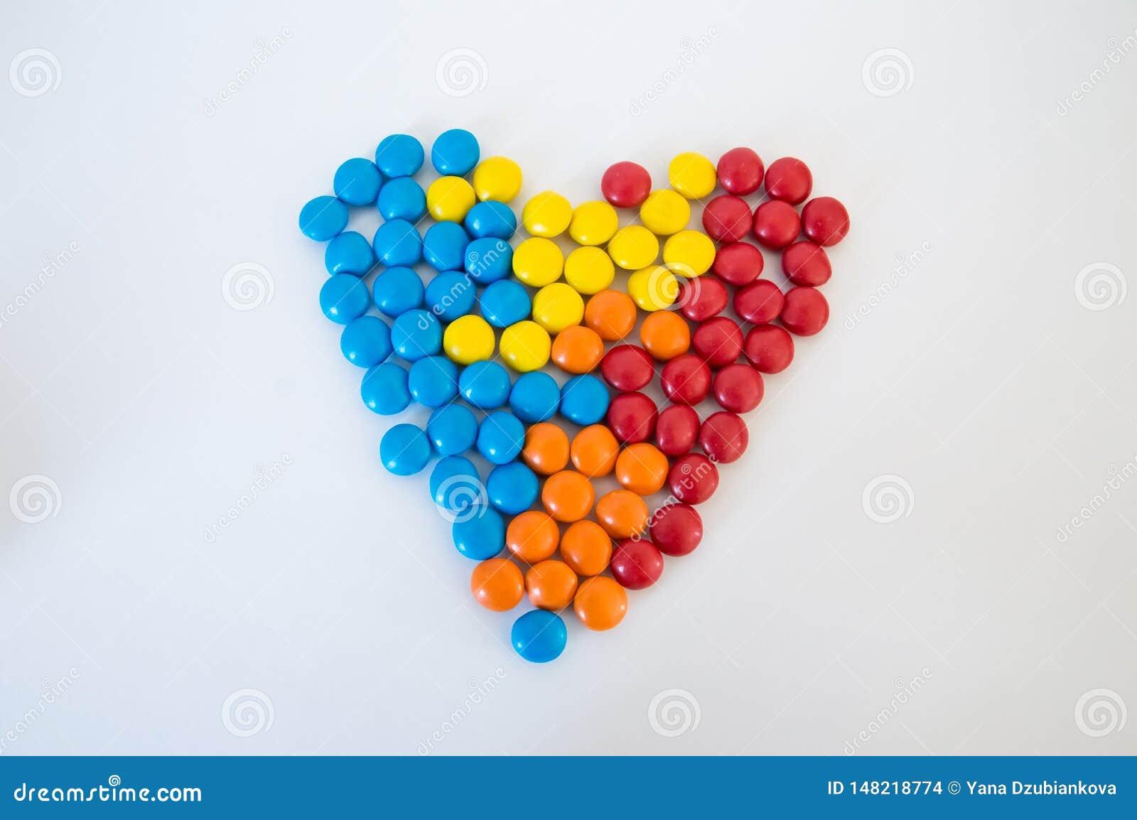 Drag?es rondes multicolores de sucreries pr?sent?es sous forme de coeur sur un fond blanc