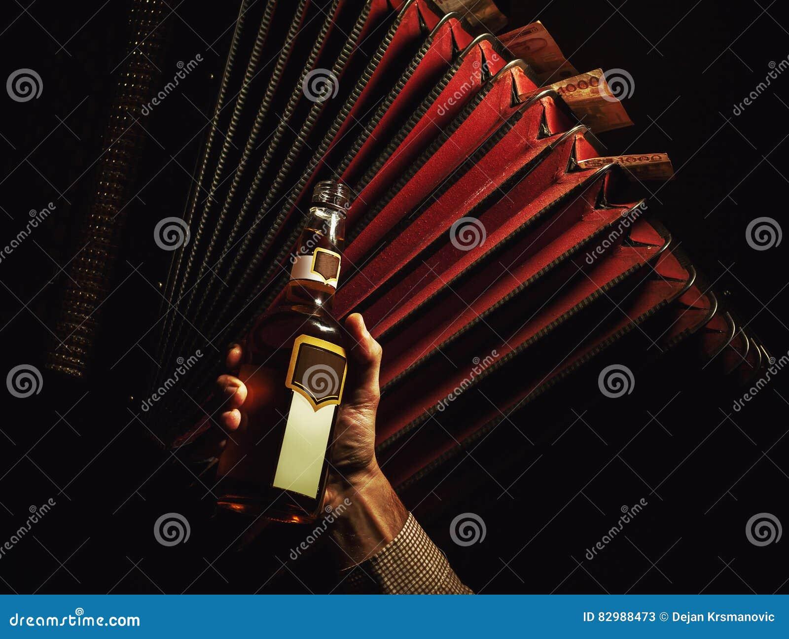 Dragspel med serbiska pengar och flaskan av drinken