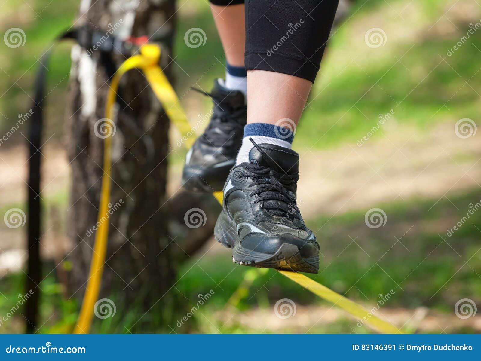 Drahtseilwanderer ist auf einem festen Riemen, der auf den Bäumen örtlich festgelegt ist, an einer niedrigen Höhe