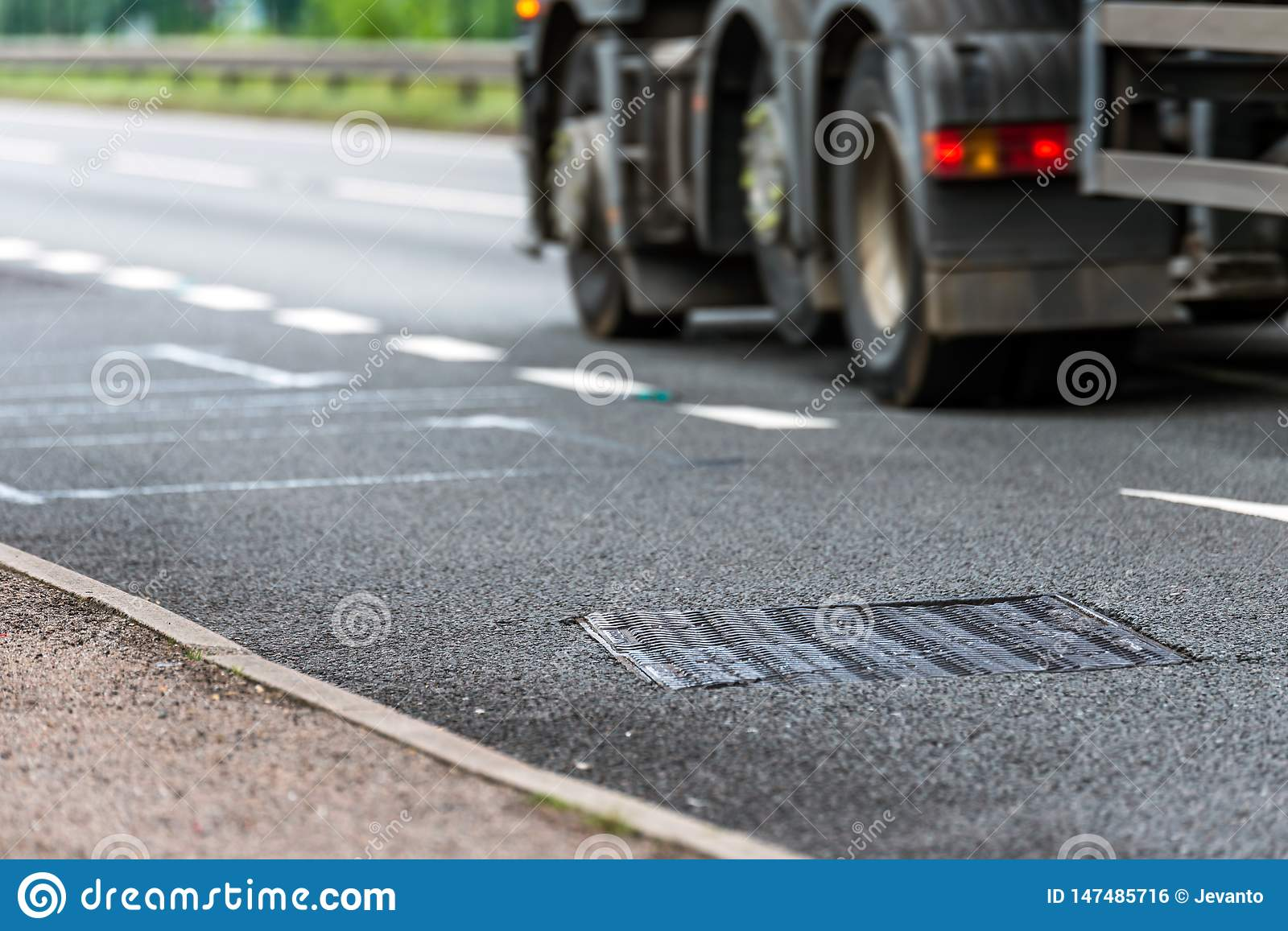 Drainage water collector system on uk motorway with truck in fast motion on background