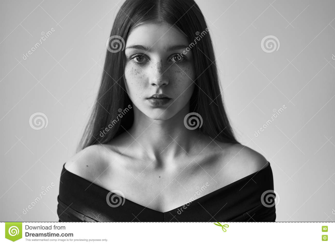 Dramatic black and white portrait of a beautiful lonely girl with freckles isolated on a white background in studio