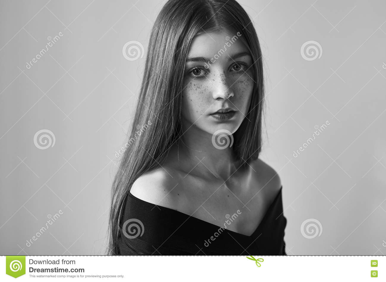 Dramatic black and white portrait of a beautiful lonely girl with freckles isolated on a white background in studio shot