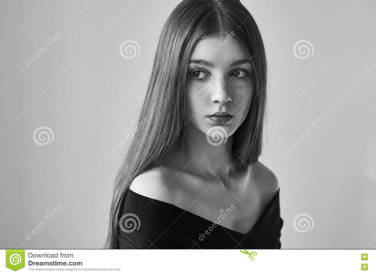 Dramatic black and white portrait of a beautiful lonely girl with freckles on a white background