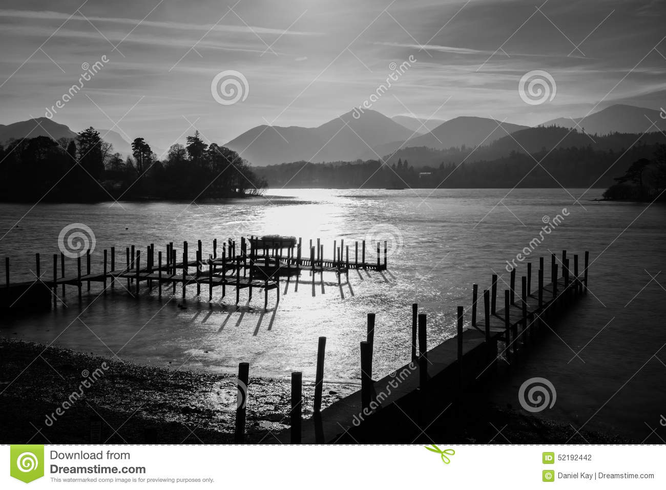 Dramatic black and white sunset at derwentwater lake in the lake district with haze over mountains