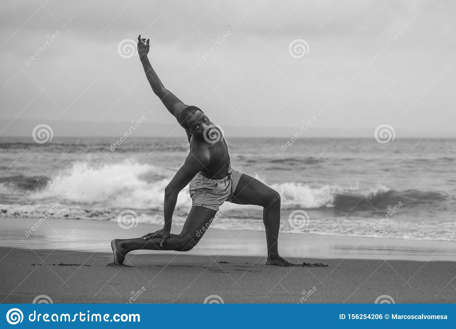 Dramatic contemporary dance choreographer doing ballet beach workout, young attractive and athletic afro black American man