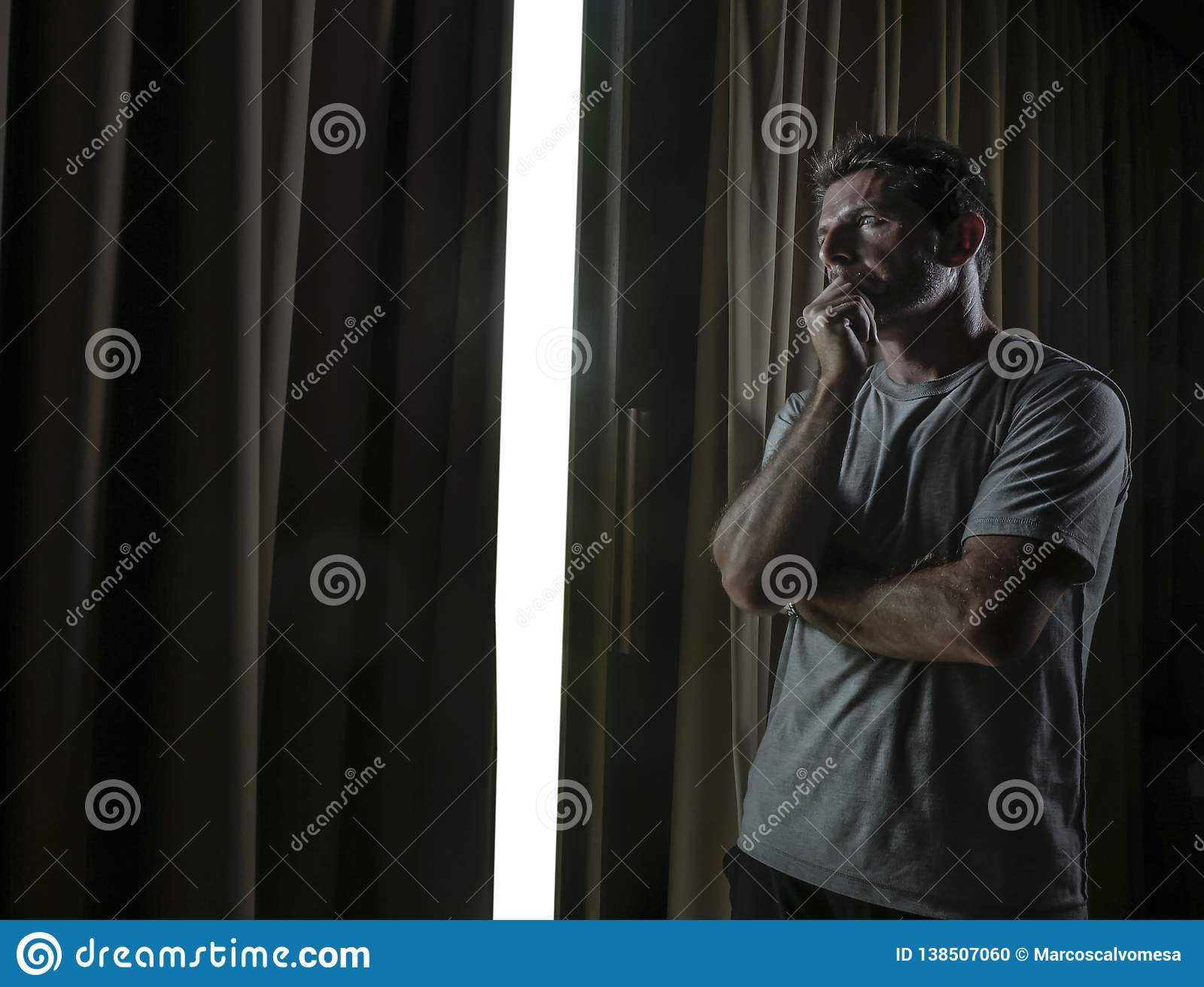 Dramatic light portrait of young sad and depressed attractive man at home looking through room window thoughtful and pensive lost