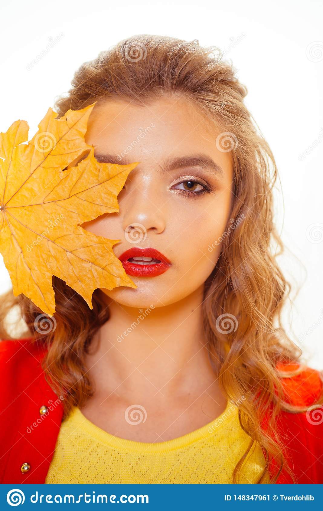 The dramatic nature of the red lipstick. Pretty girl cover face with autumn leaf. Fashion model with decorative fall
