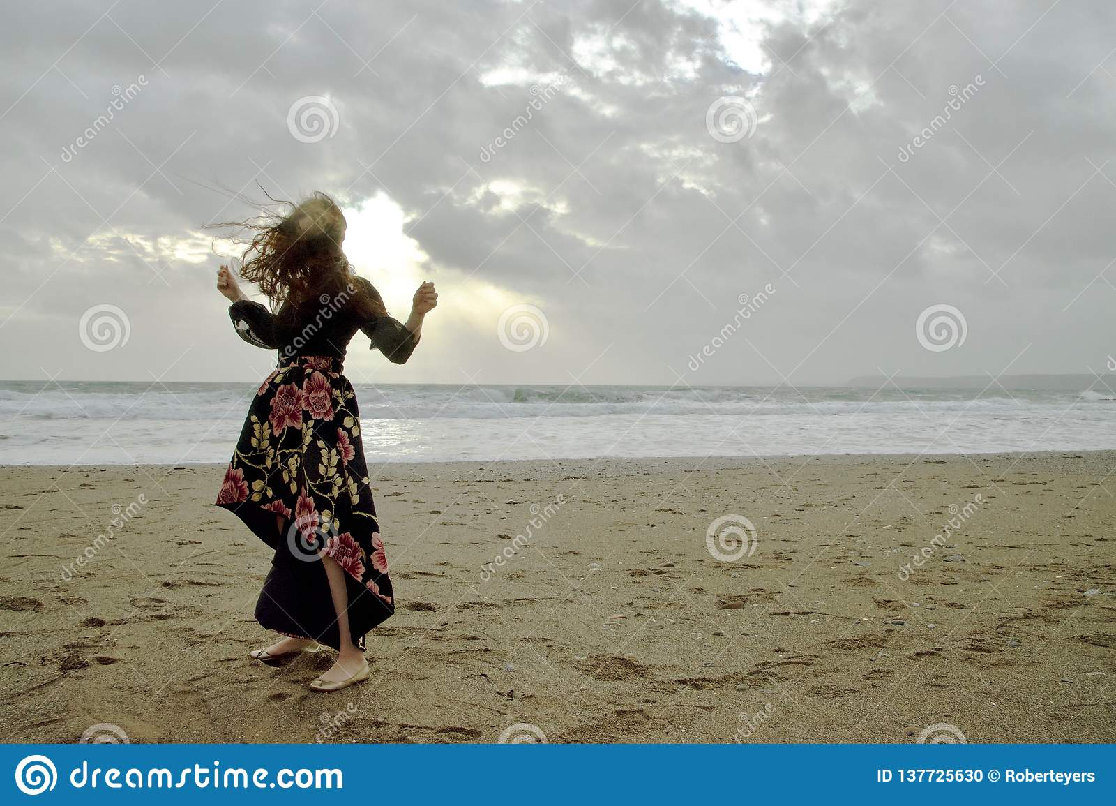 Dramatic portrait of long haired lady in floral formal dress on a stormy beach in front of the sun