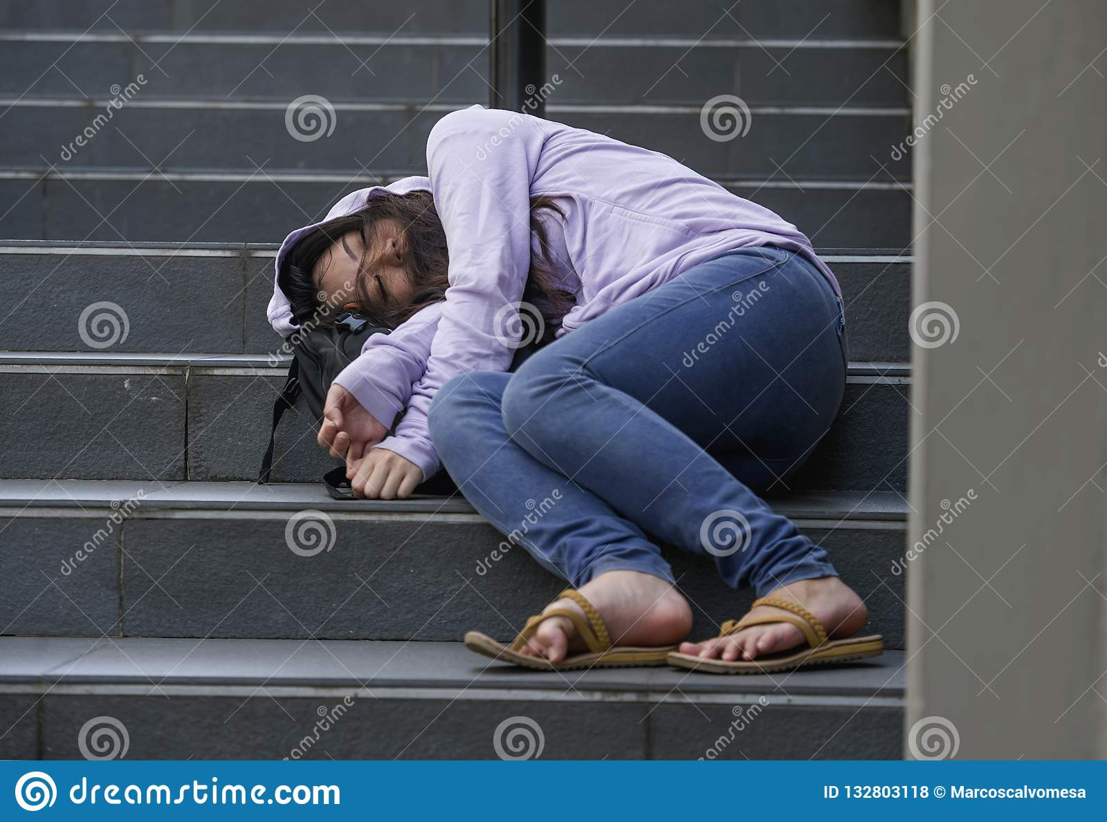 Oung depressed and intoxicated Asian student woman or teenager girl sitting on street staircase drunk or high on drugs suffering