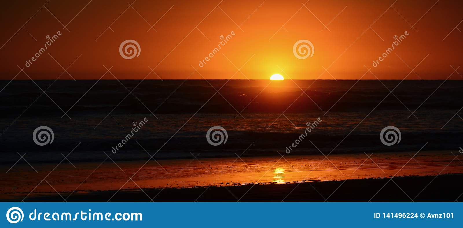 Dramatic sunset colours; beautiful sunset on a beach. Sun reflection in the water.