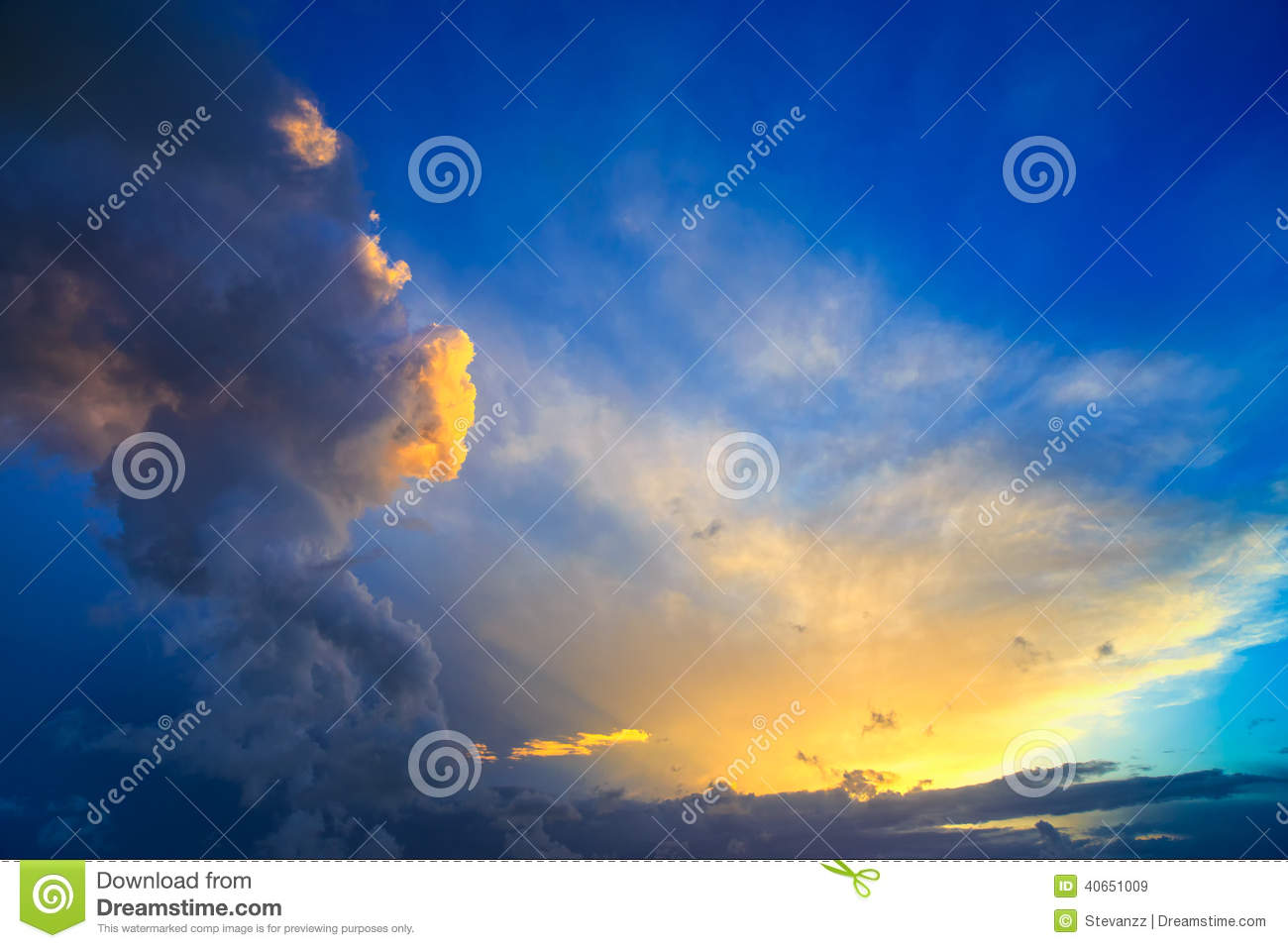 Dramatic sunset sky with yellow, blue and orange thunderstorm cl