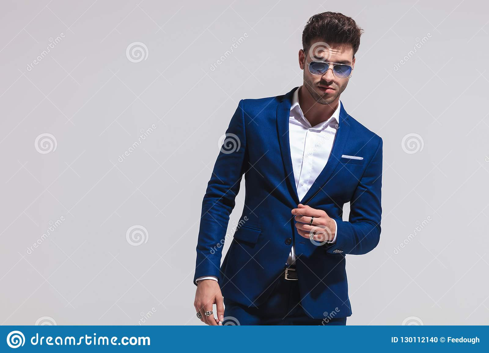 62e7be57fb63 Dramatic young fashion man in suit and sunglasses posing on grey studio  background