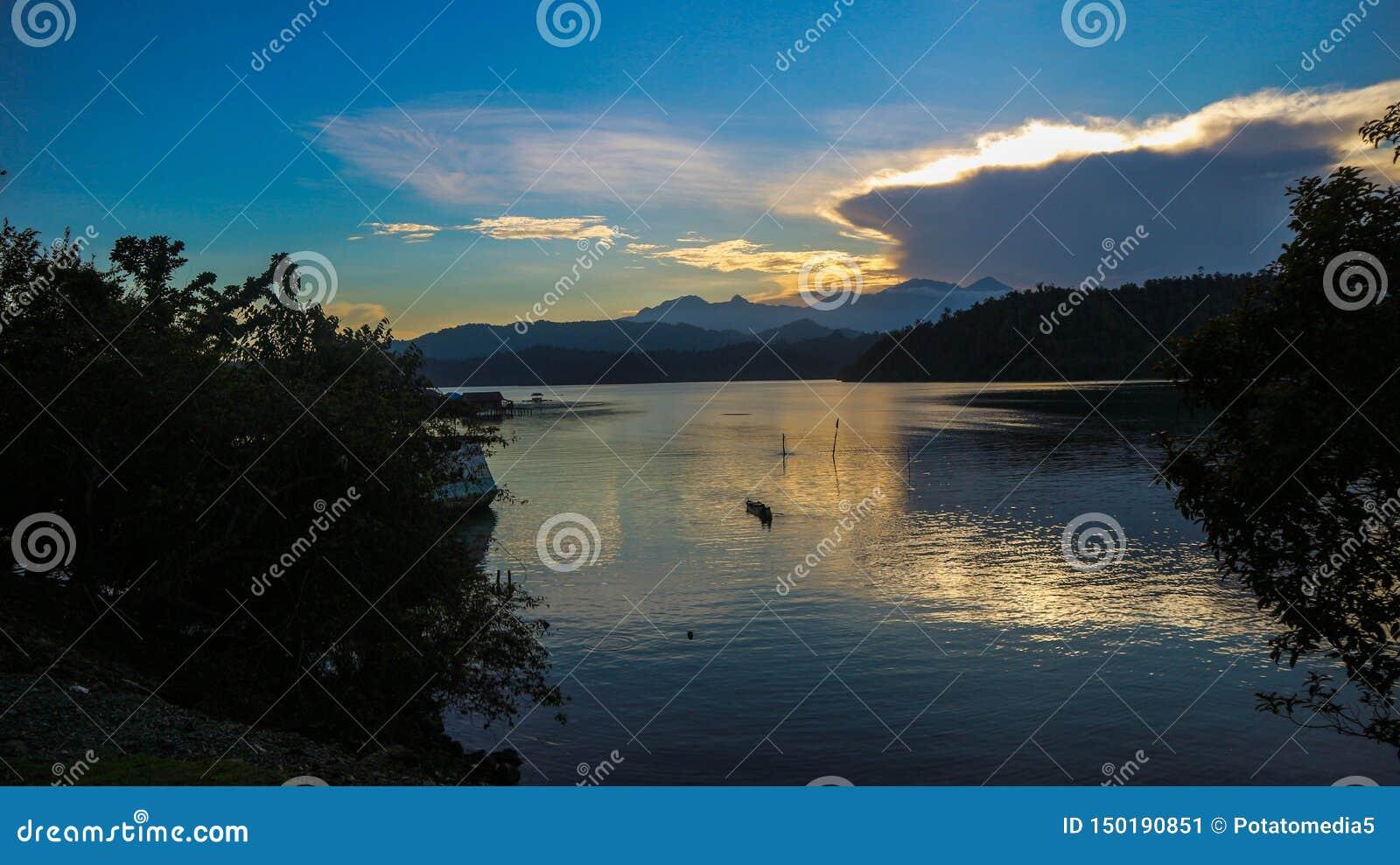 Dramatisk sikt av solnedgången med berghavsbakgrund