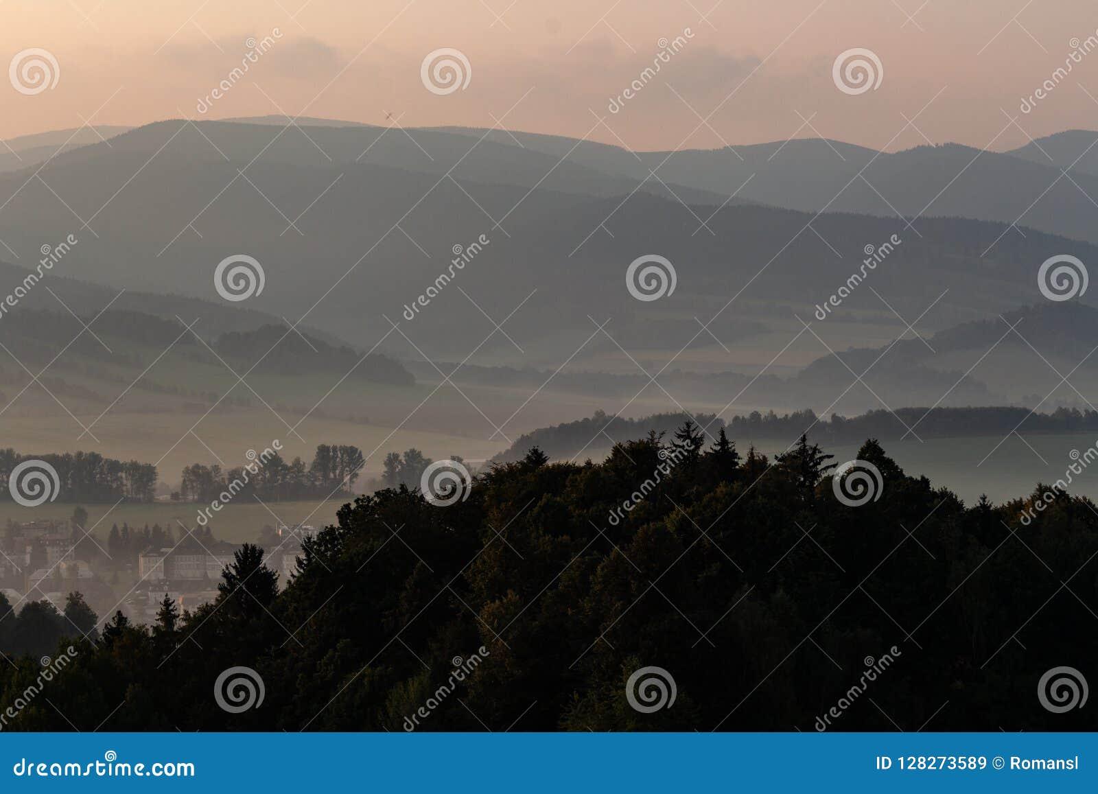Dramatisk sikt i bergen för stormen - skurkrollgrå färgmoln svävar över gröna bergkanter