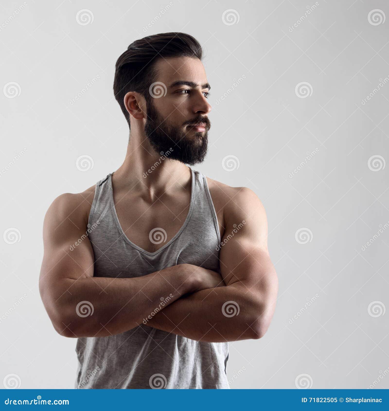 Dramatisk stående av den säkra starka stiliga skäggiga idrottsman nen med korsade armar