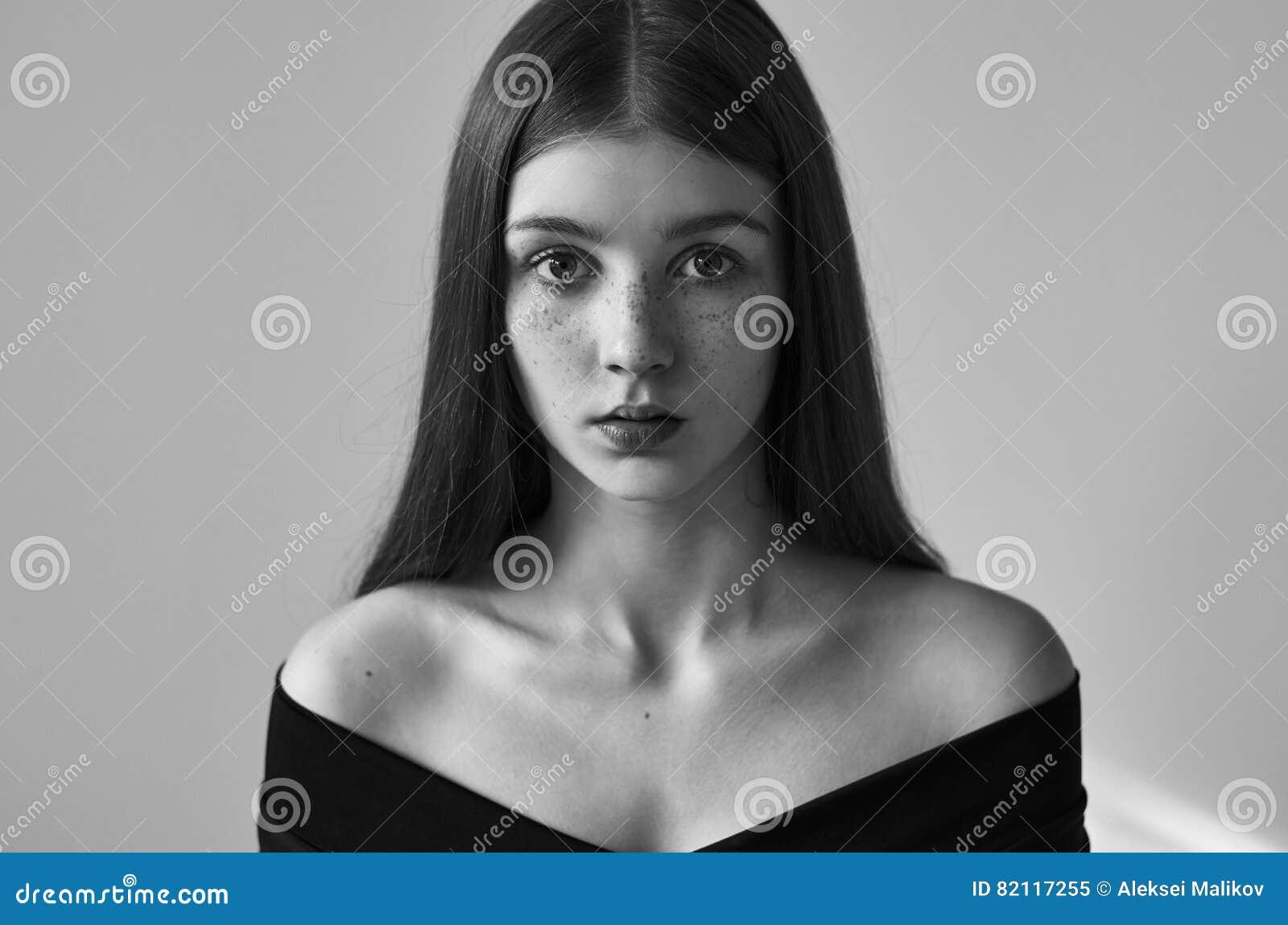 Dramatisk svartvit stående av en härlig ensam flicka med fräknar som isoleras på en vit bakgrund i studioskott