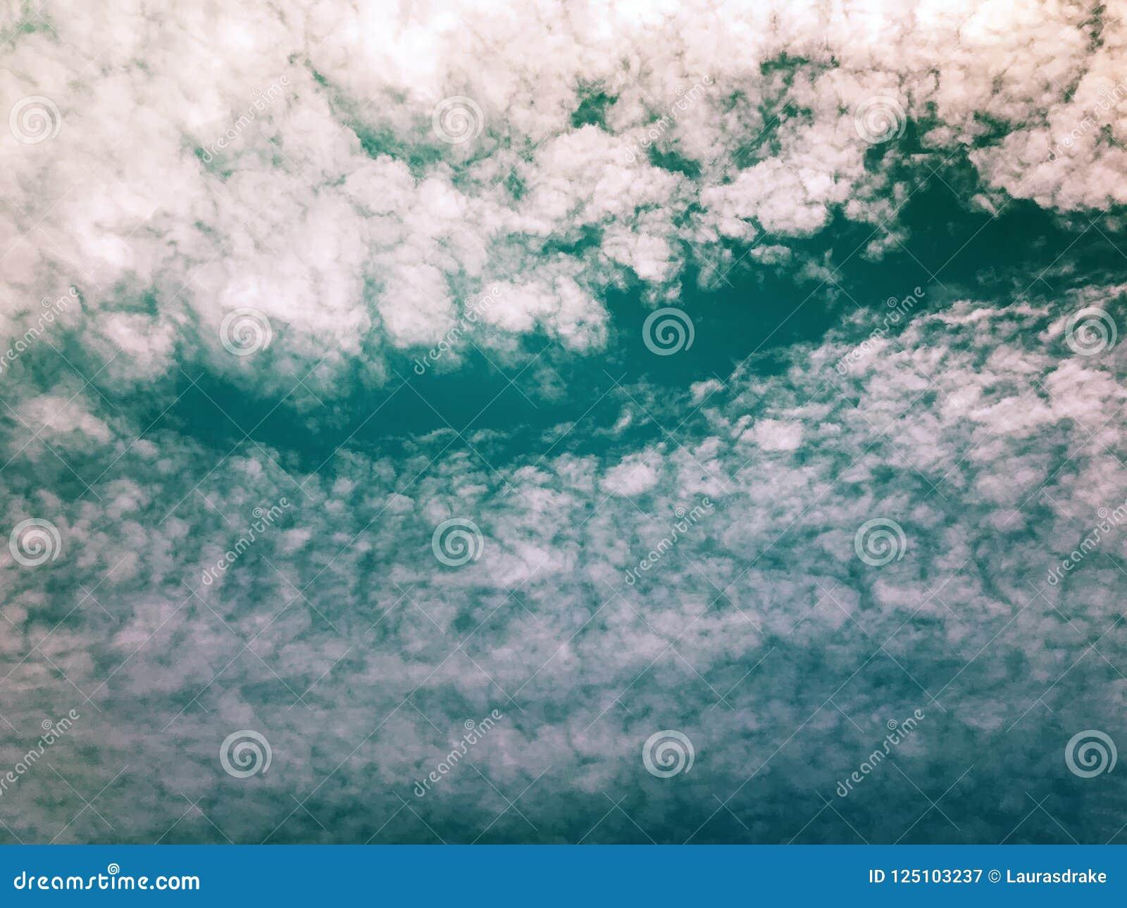 Dramatiska stackmolnmoln med blå himmel som igenom kikar