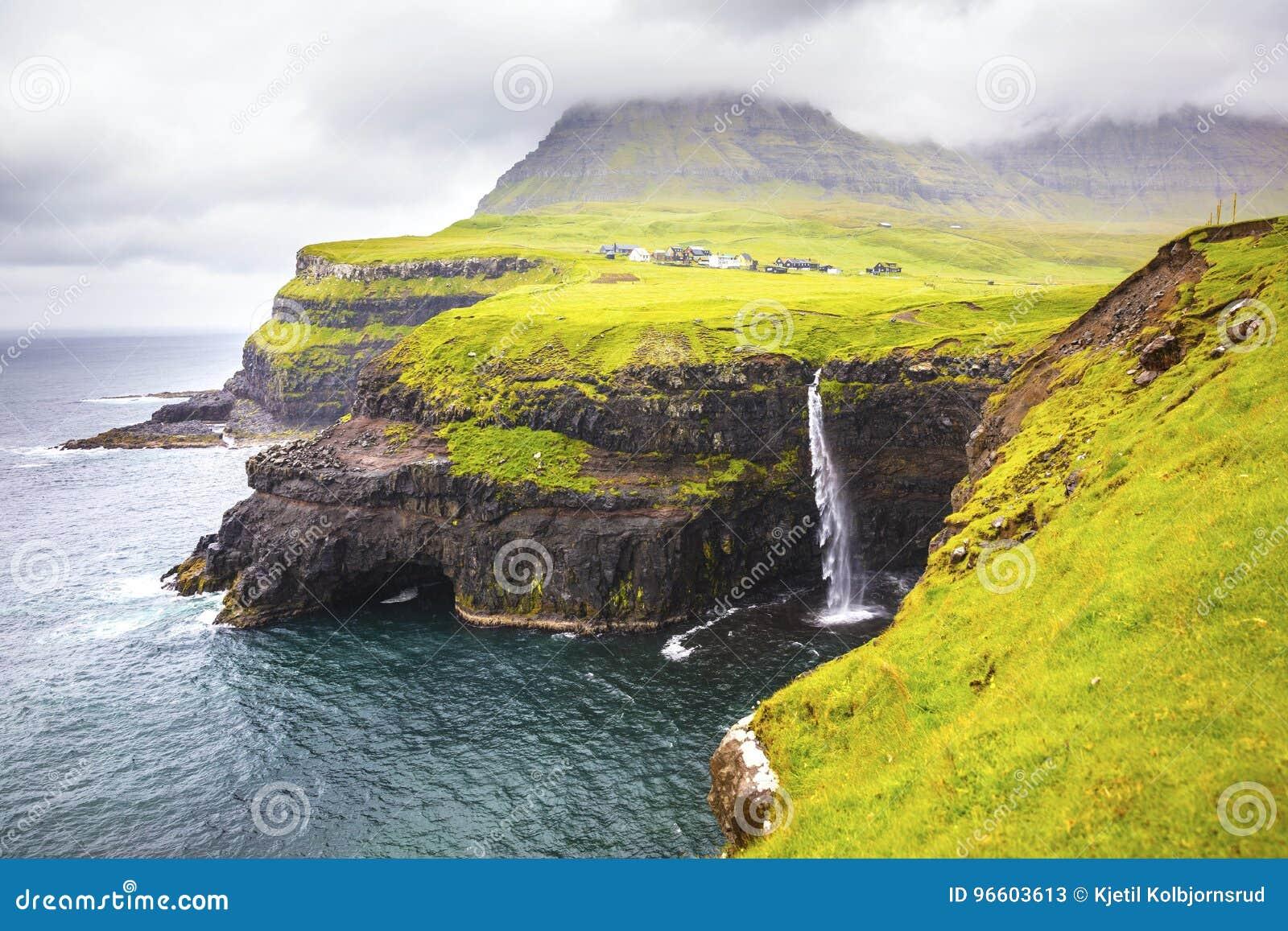 Dramatyczna siklawa na Faroe wyspach Gasadalur i wiosce