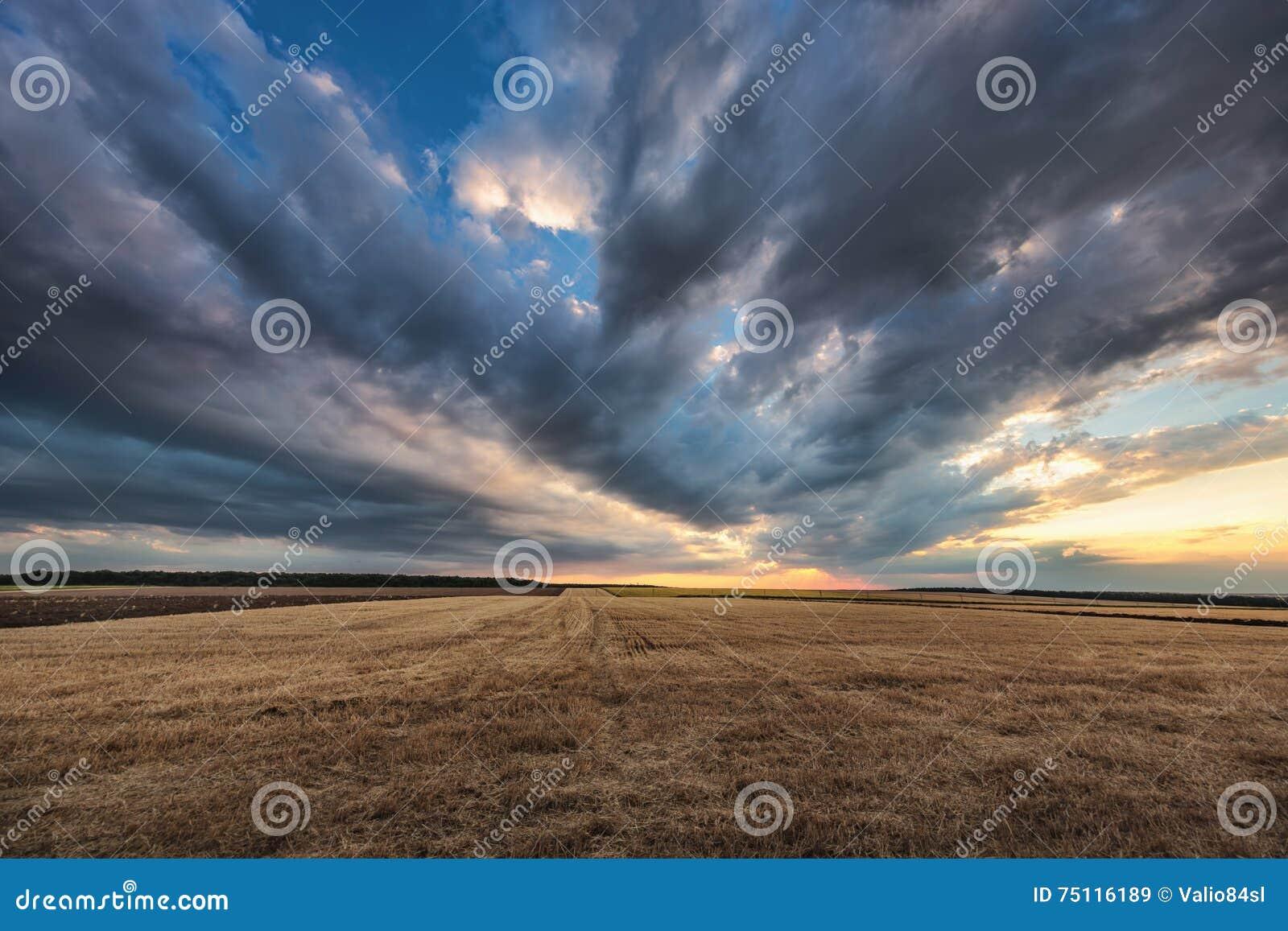 Dramatyczne chmury nad polem po żniwa