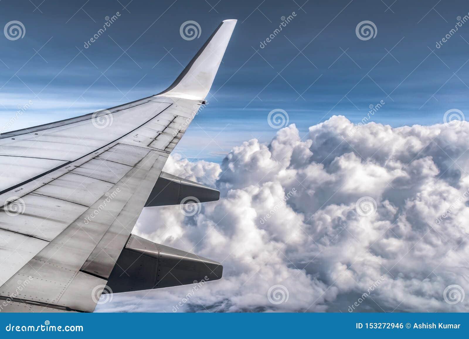 Dramatyczne chmury od okno samolot Skrzydła i wszystkie składniki są widoczni Chmurnieje puszystego jako bawełniane piłki
