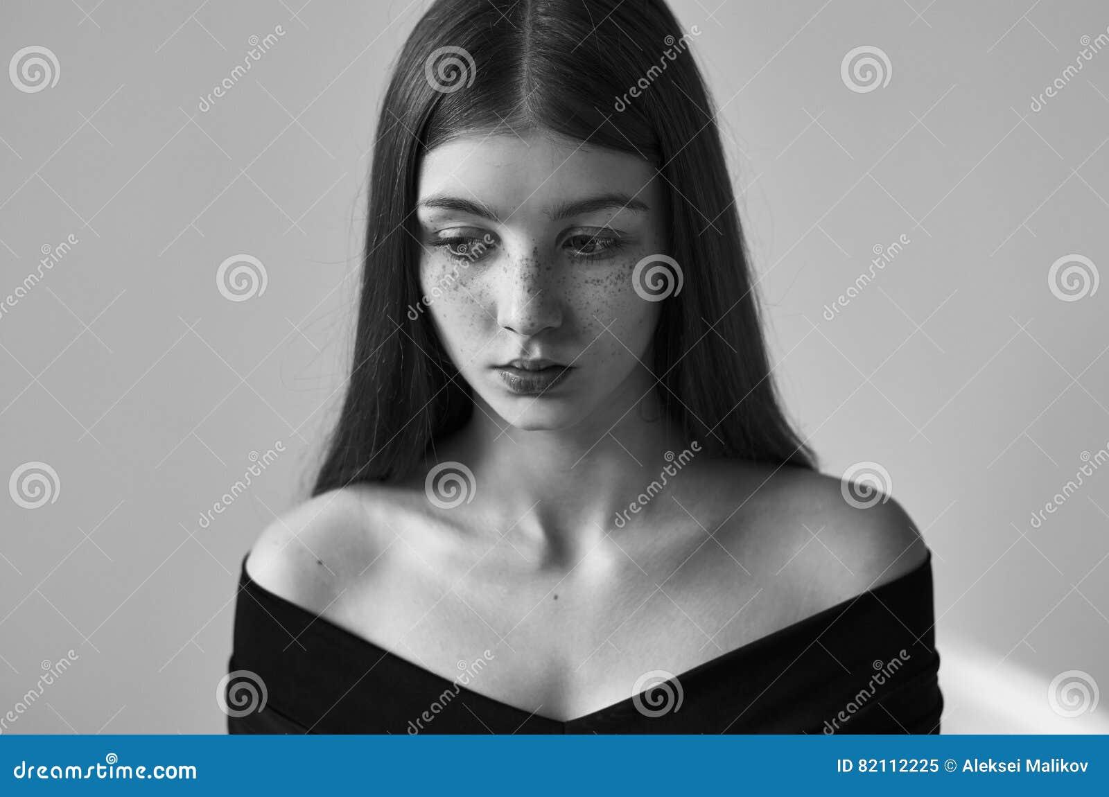Dramatyczny czarny i biały portret piękna osamotniona dziewczyna z piegami odizolowywającymi na białym tle w studio strzale
